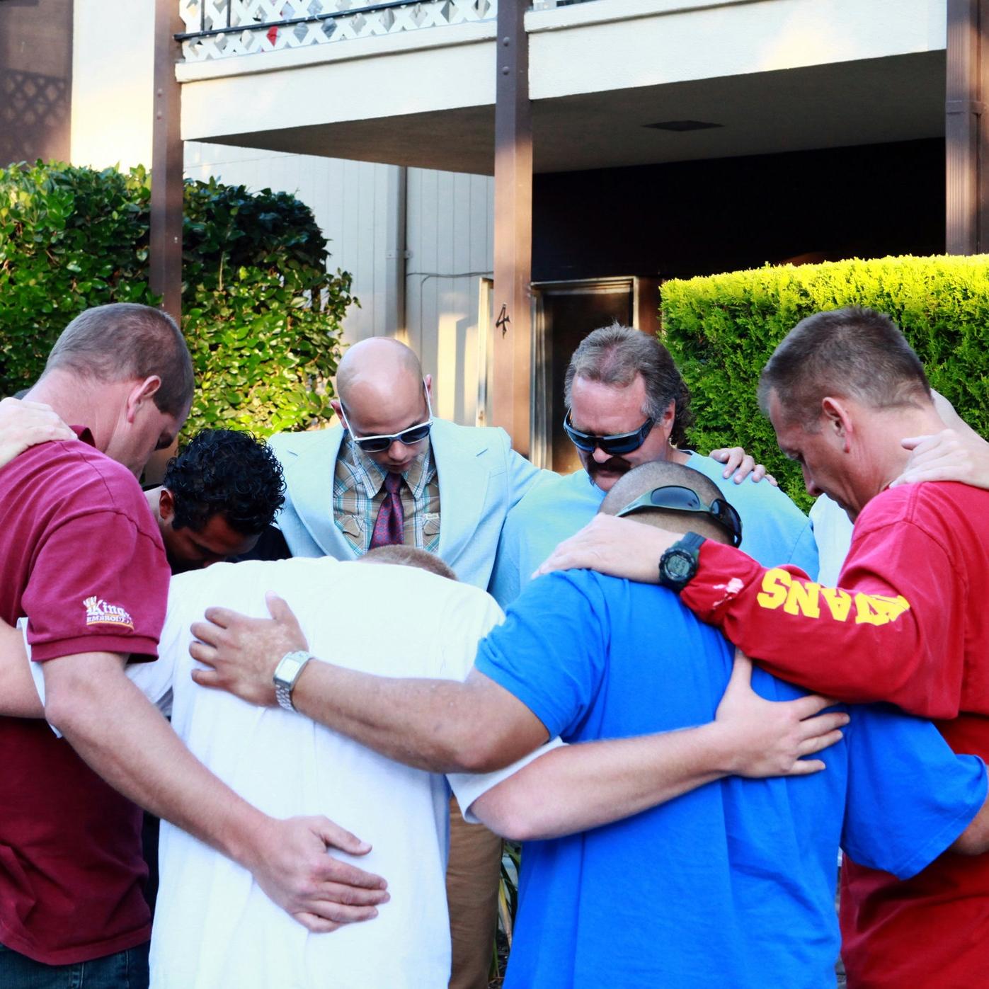 Men at the Sacramento Re-Entry Center for Men, praying in a group.