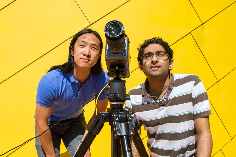 2015 photo of Graduate students Justin Chen and Neal Wadhwa setting up a video camera