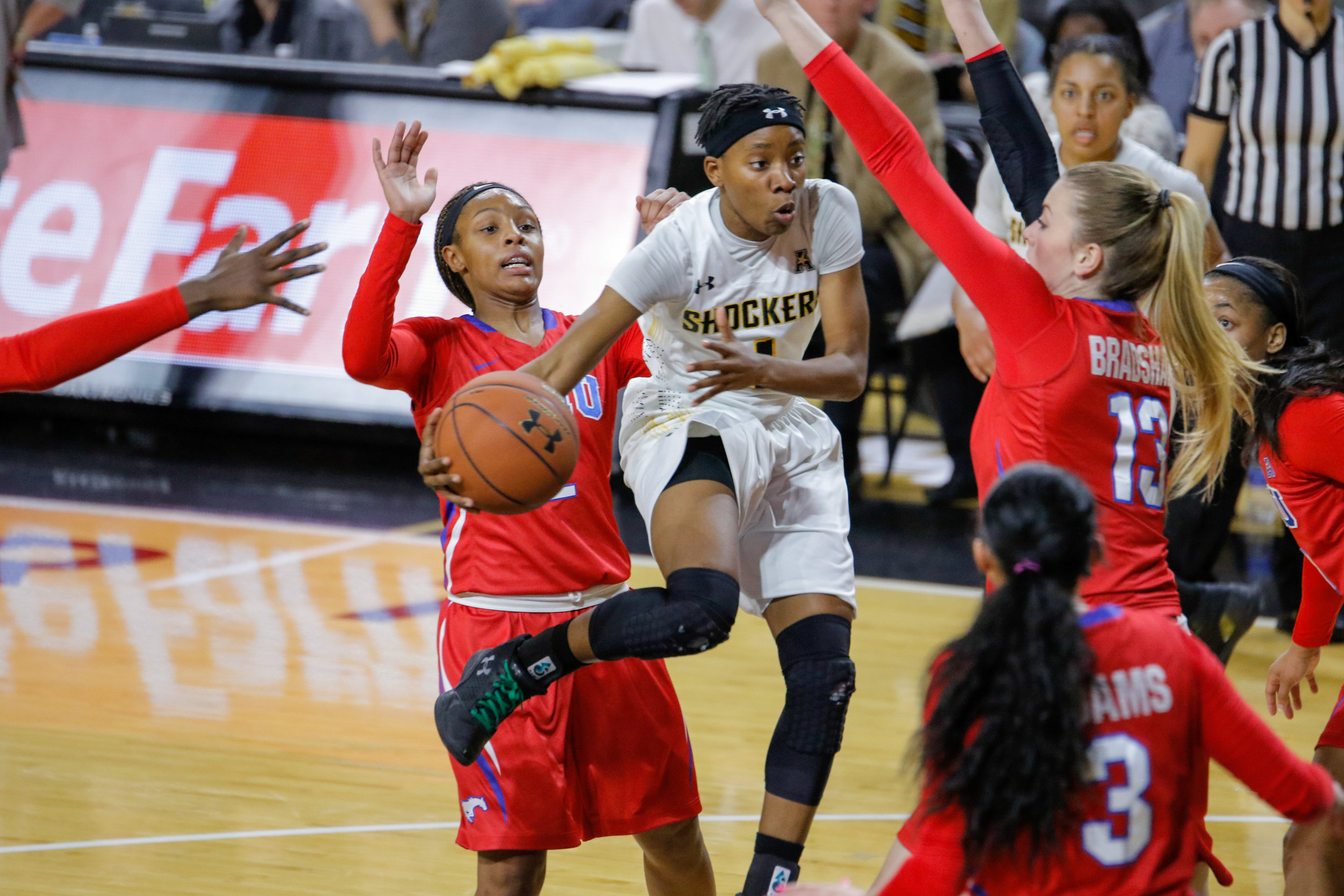 Wichita State's Keke Thompson passes while heavily guarded against SMU on January 16, 2018 at Charles Koch Arena.