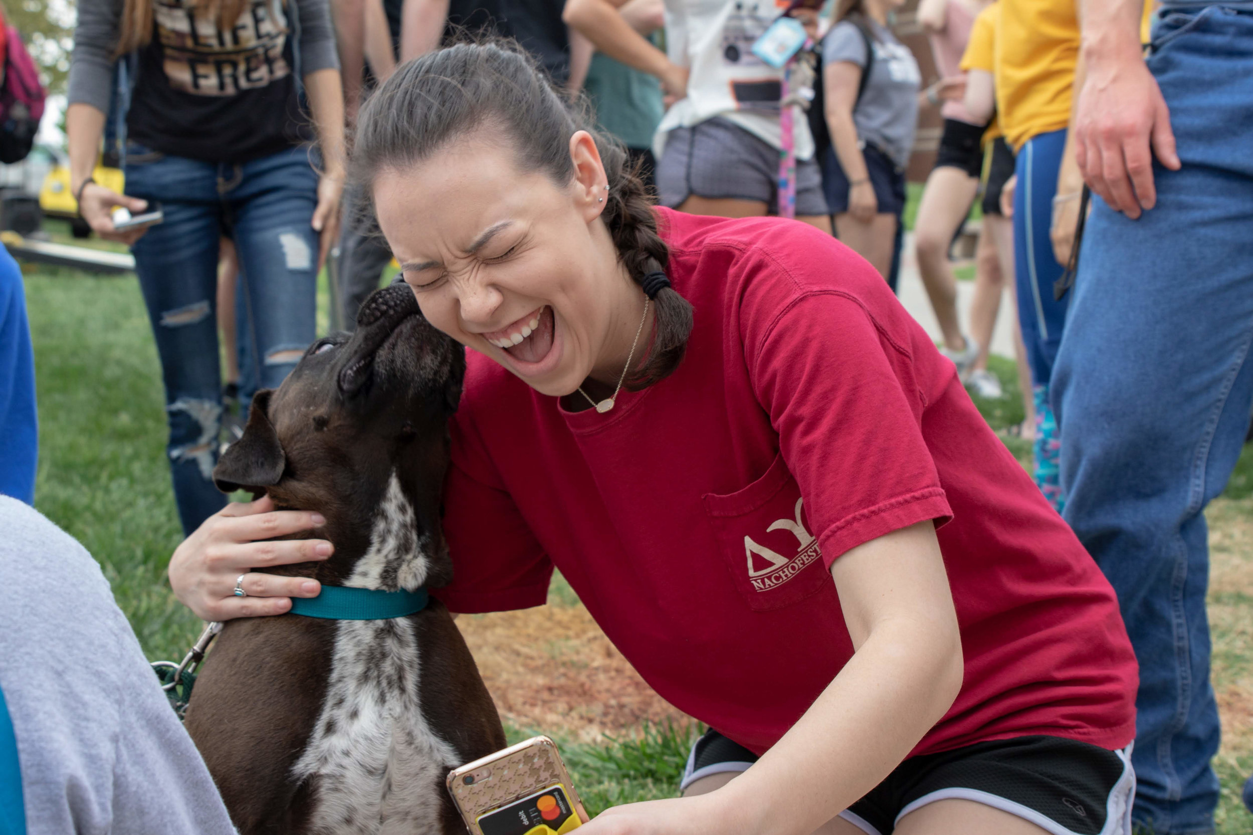 """Students pass by """"Dogs with DU"""" on May 2, 2018 on the campus of Wichita State University."""