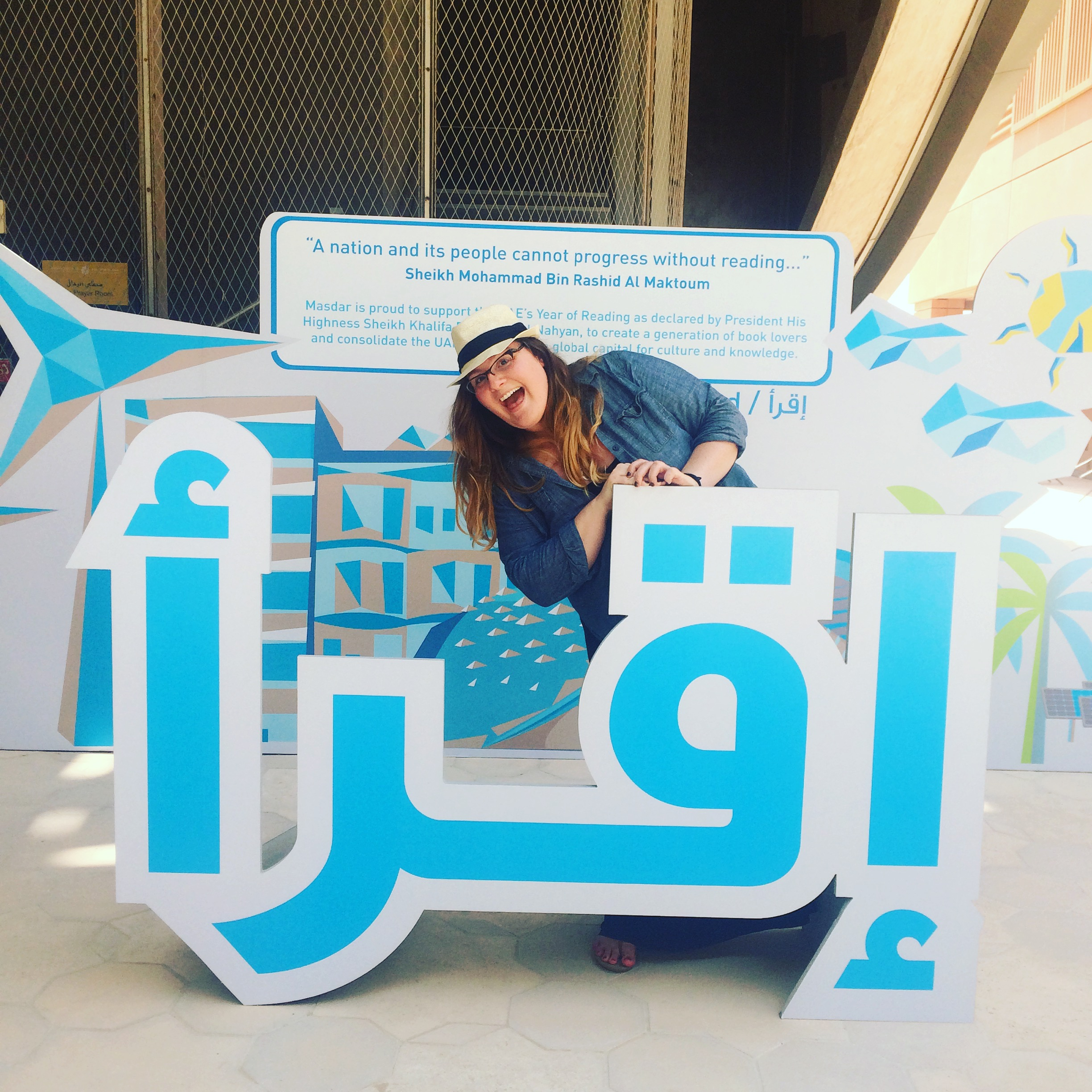 "Amber loves all forms of literacy (as she demonstrates here in Abu Dhabi, UAE by posing behind a sign that says ""Read!""), but she loves science literacy most of all."