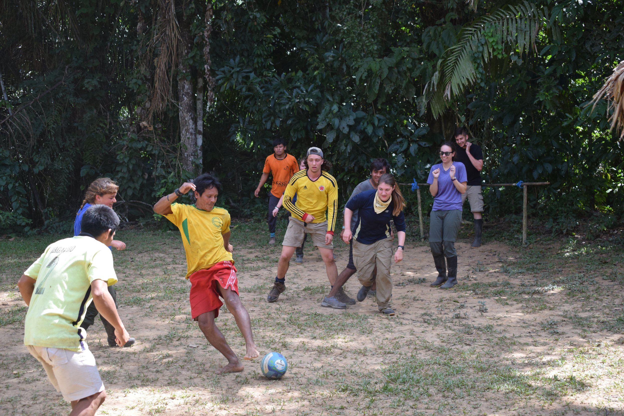Trip participant playing soccer with some of the locals.
