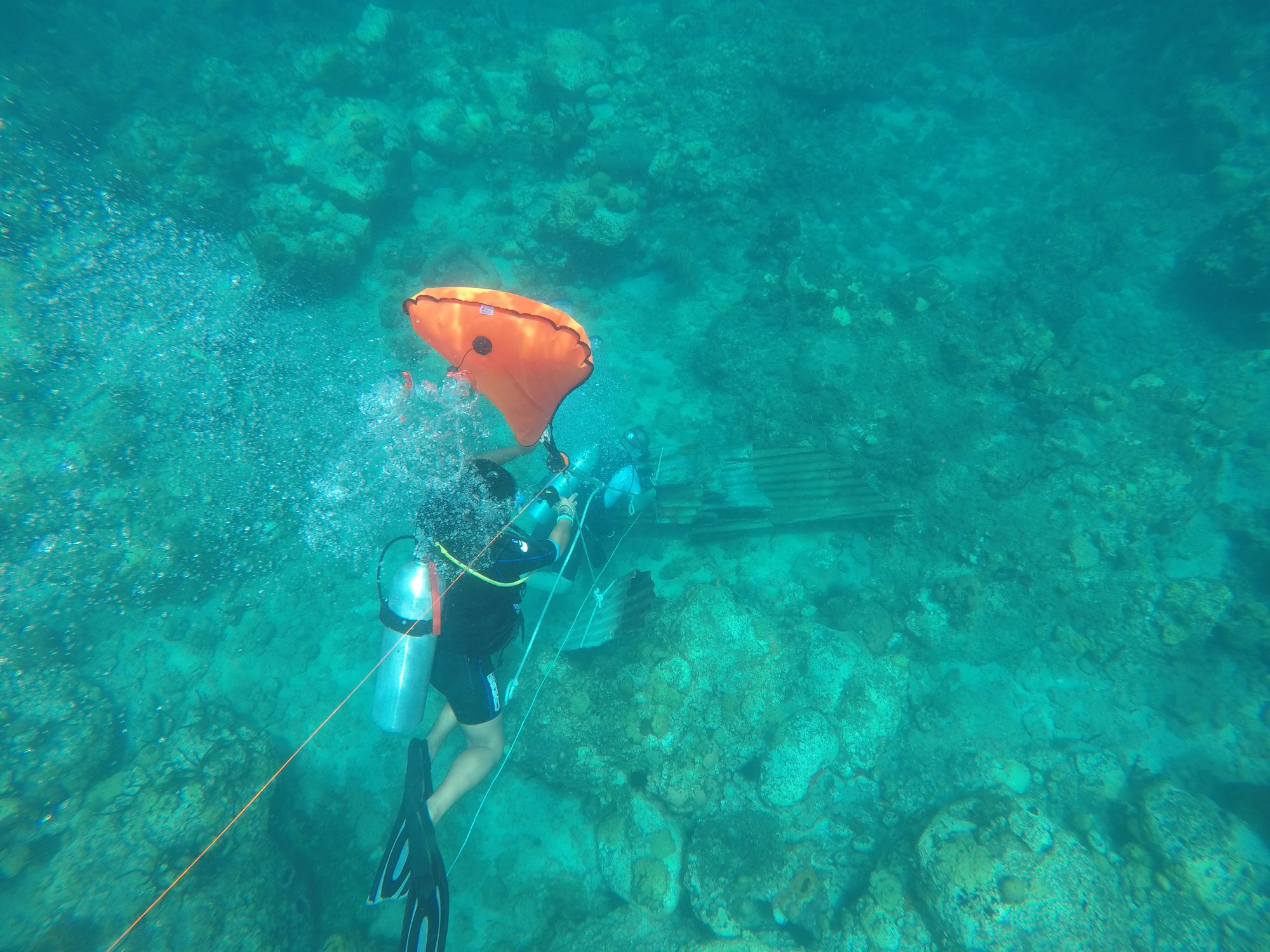 Our Divemaster Joy rigging a surface line to the lift bag line, and Diver Bill securing the pile of galvanized roofing below!