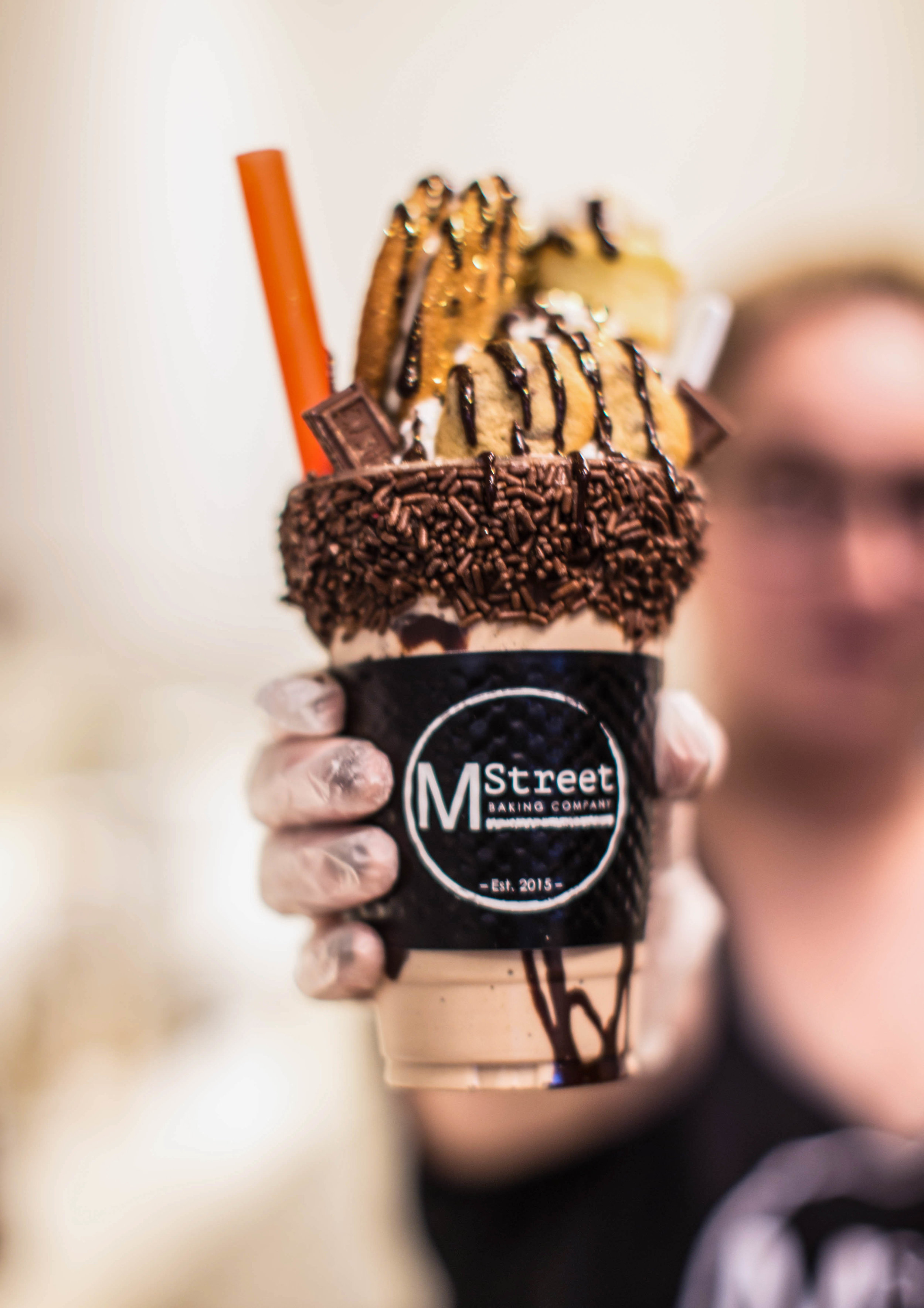 """The """"Chocolate Trip"""" is a chocolate flavored shake topped with:  Whipped Creme, Mini Cupcake, Chocolate bars, Cookies, Chocolate Drizzle."""