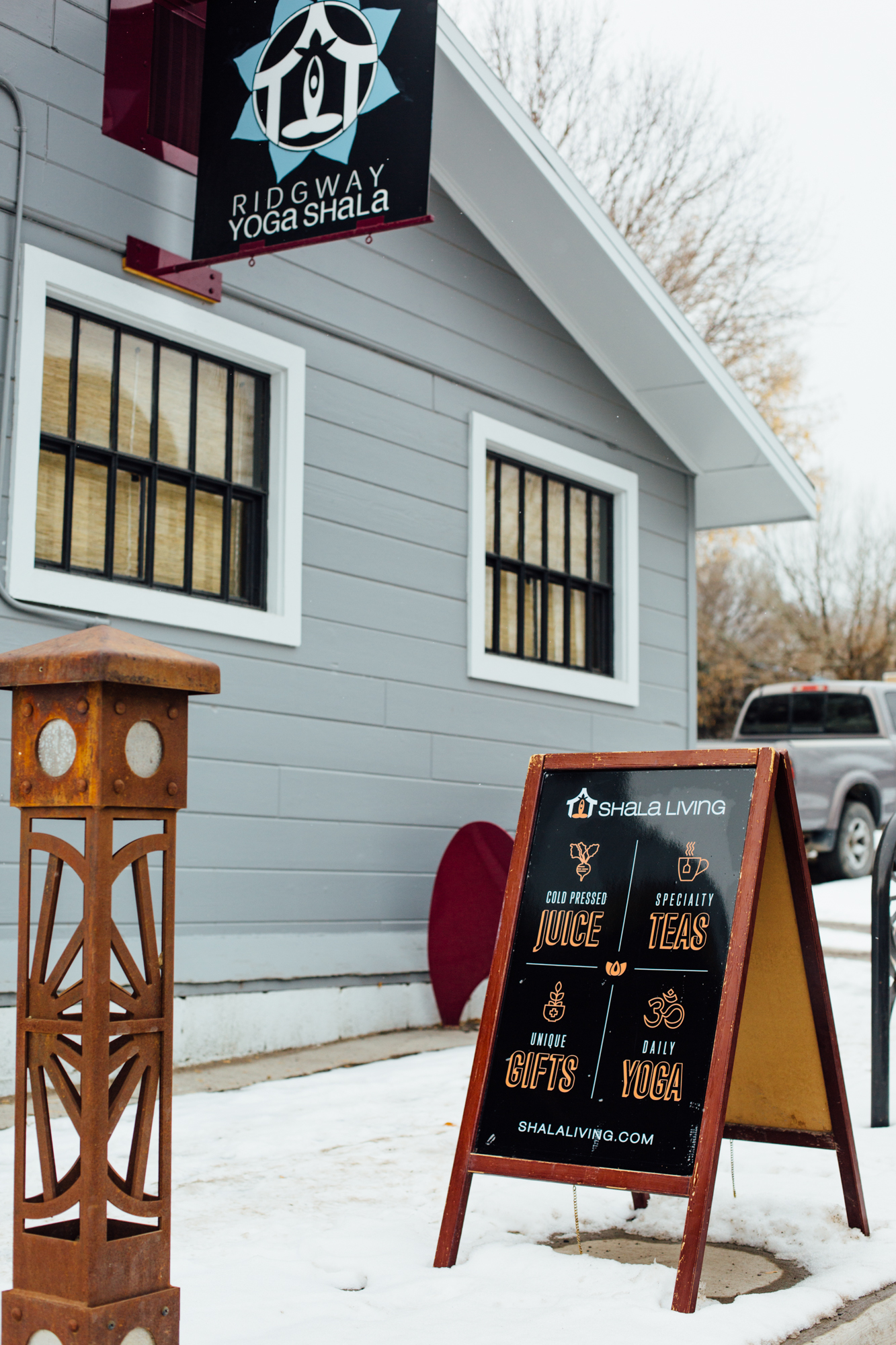 A sandwich board Sitting outside of the Ridgway Yoga Shala with graphics we designed