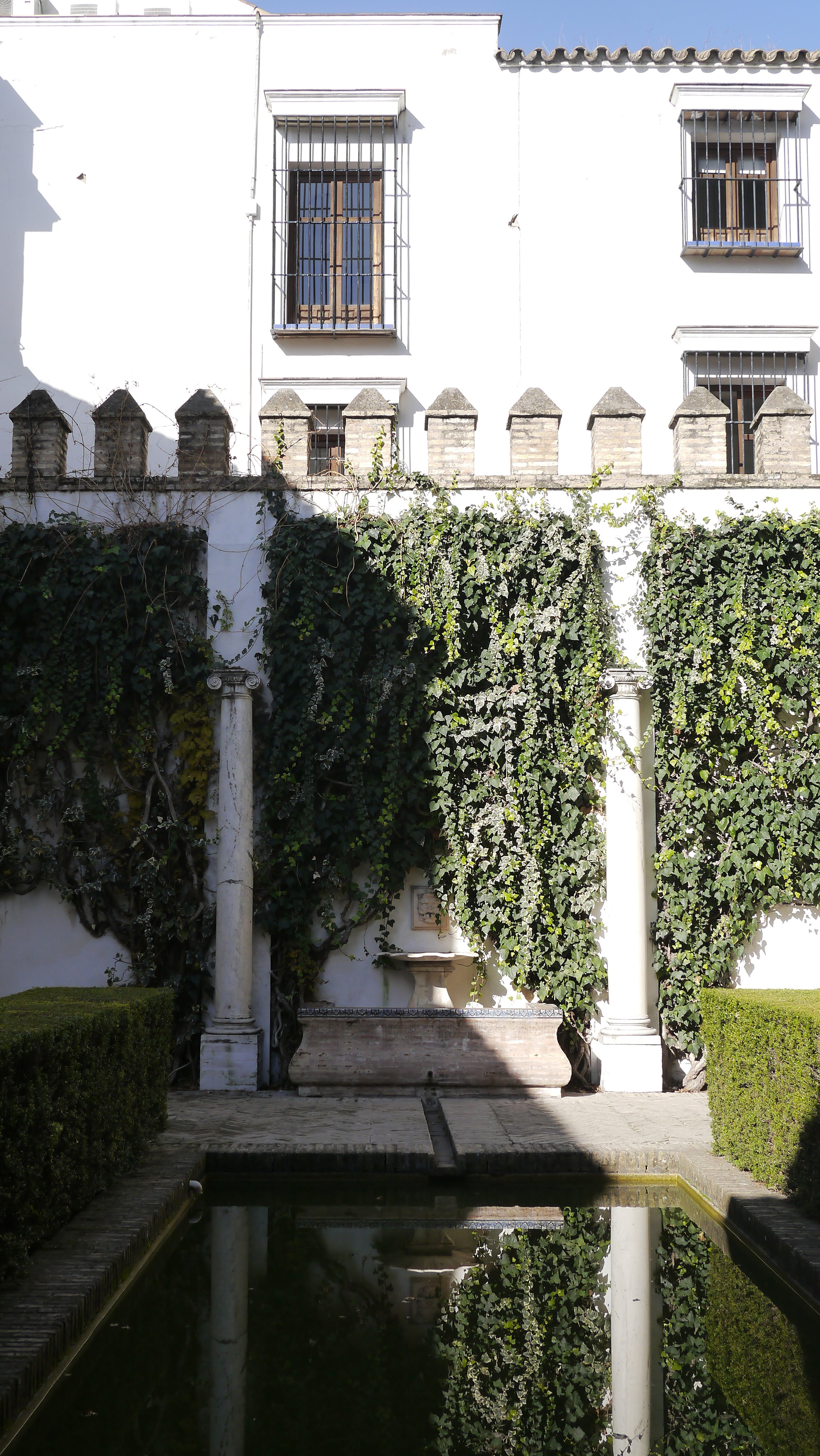 Reflections and linear design in a quiet courtyard of the Real Alcázar, Seville, Spain. December 2016.