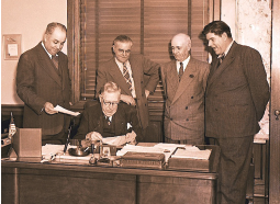 "Eloi Amar, left, as General Manager of the Port of Long Beach confers with his harbor commission. Commissioner W. R. ""Frosty"" Martin is seated at the desk. Photo courtesy of Port of Long Beach."