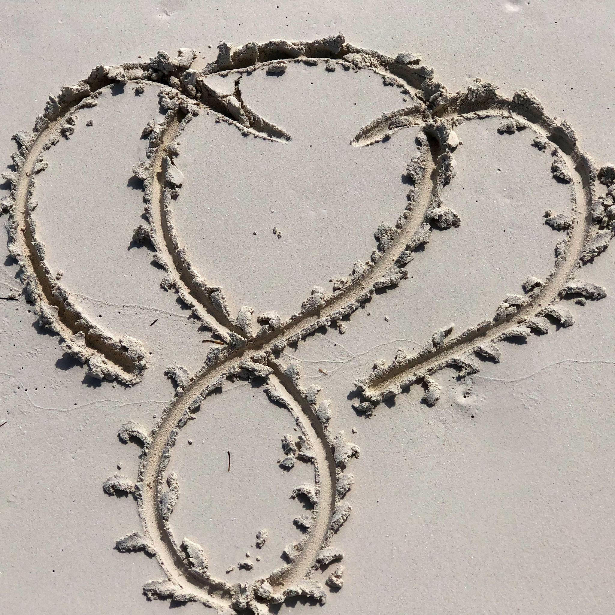 Infinite Love Logo of heart and infinity loop on sandy beach by Big Lovie
