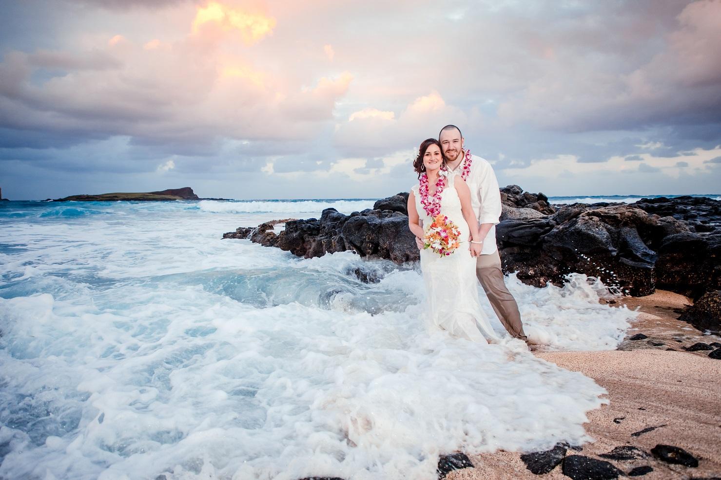 bride and groom wedding portrait in ocean waves beach sunset rocks