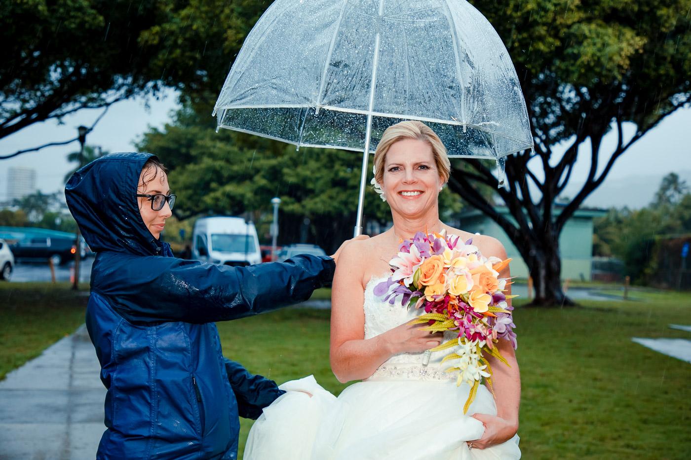bride walking down aisle in rain under umbrella oahu hawaii