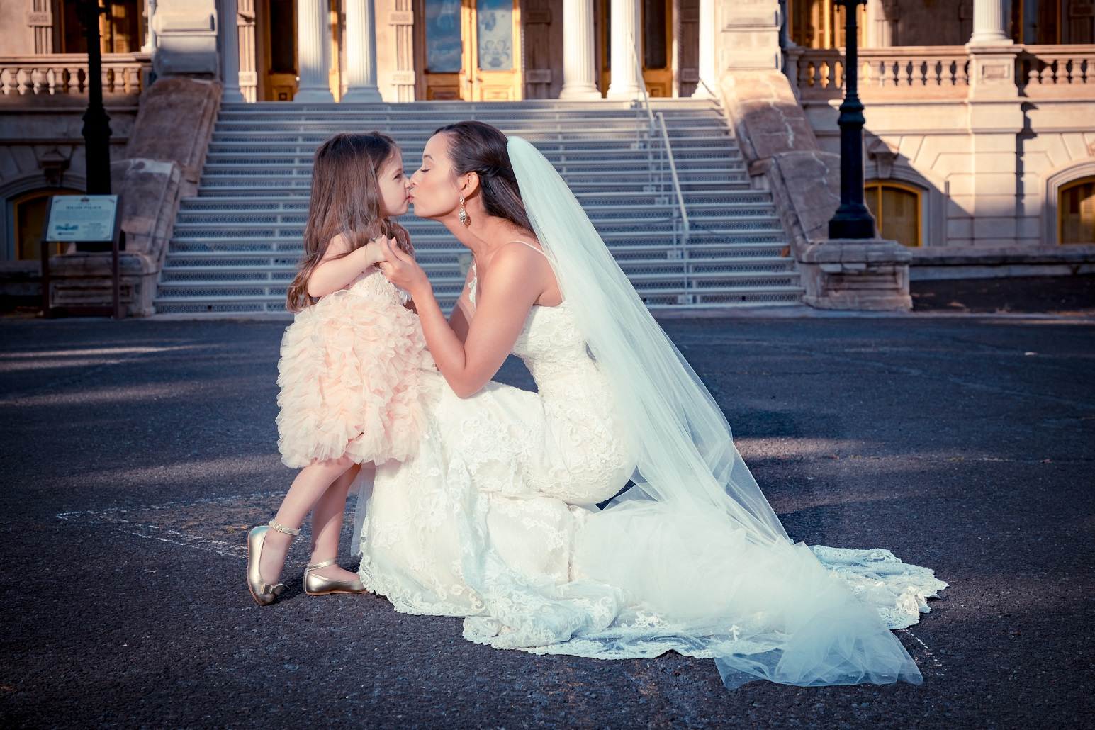 Spontaneous kiss by flower girl during bridal portraits, flashed
