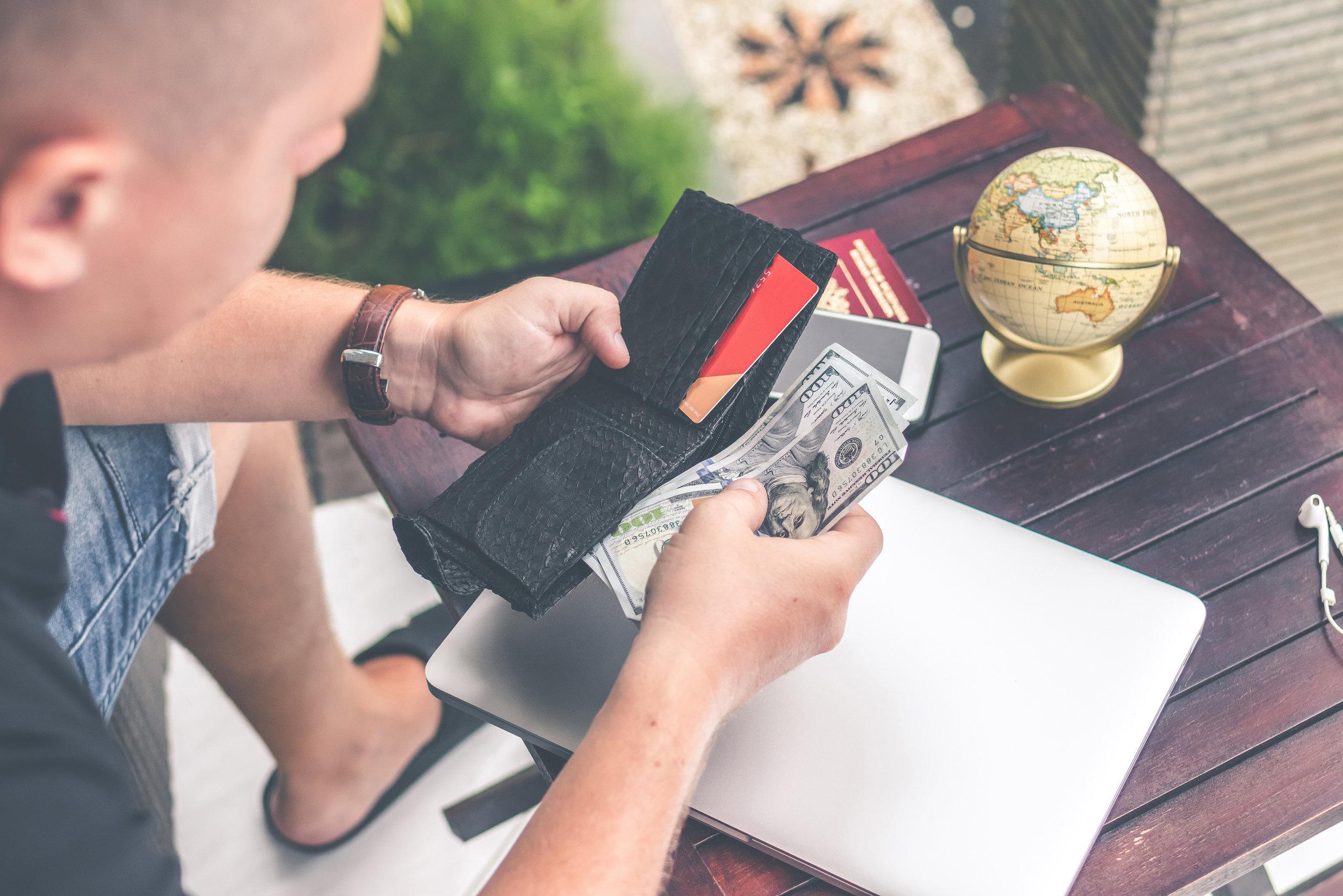 Canva - Man Holding U.s Dollar Banknotes and Black Leather Bi-fold Wallet.jpg