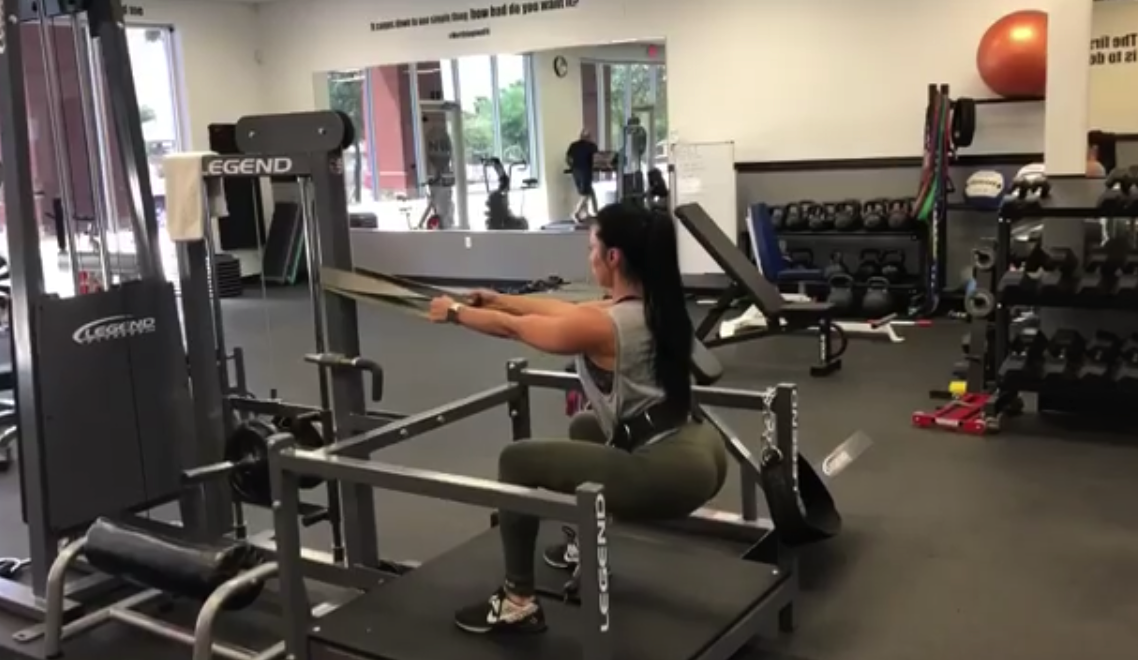 Gettin Low - Co-owner and personal trainer Karey Northington demonstrates a floor squat using a resistance band.