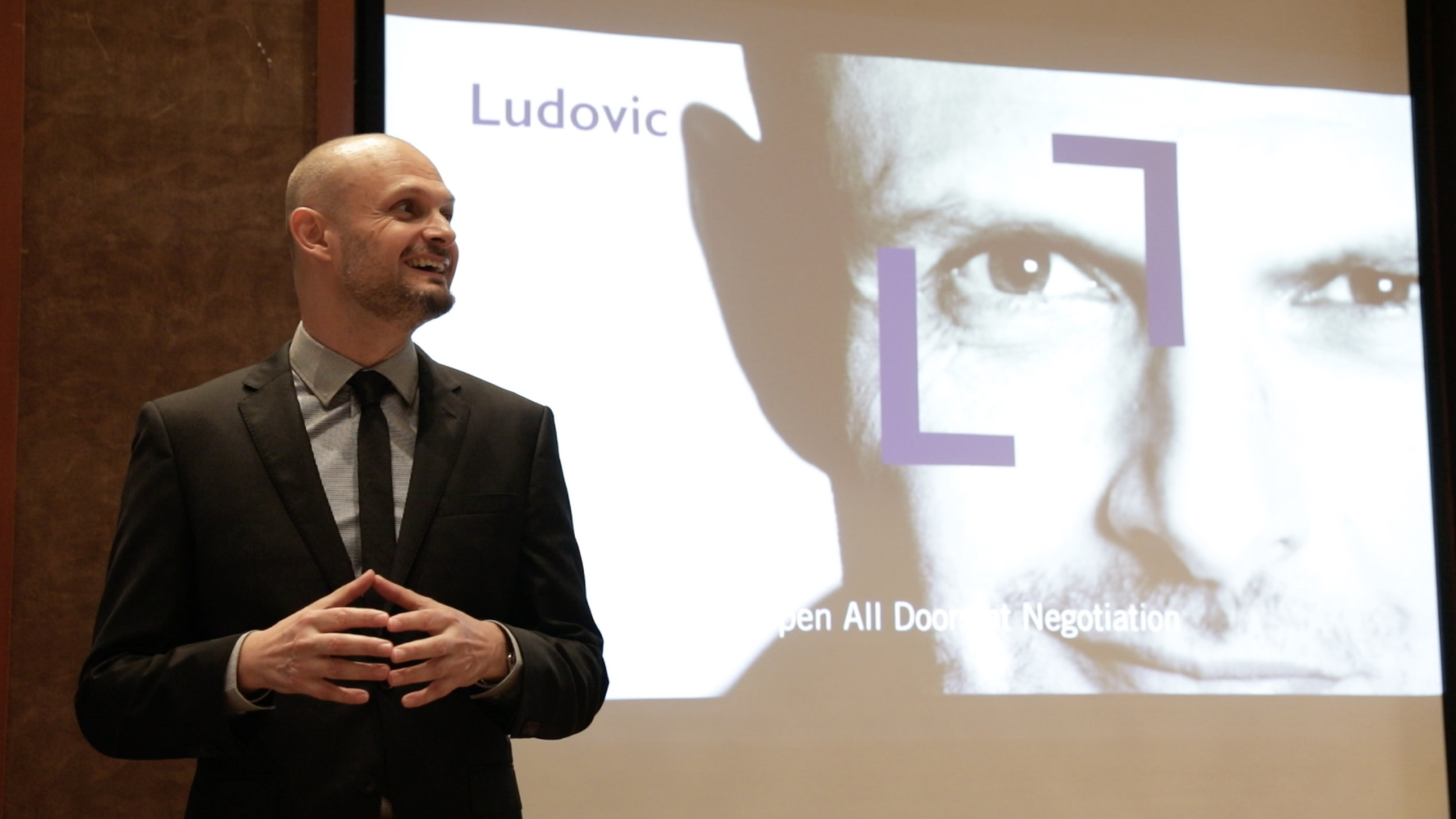 Ludovic Tendron on stage giving speaking engagement on negotiation