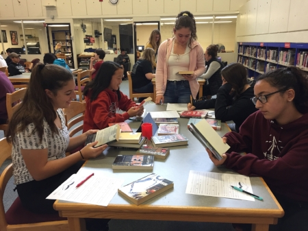 """Ms. Smetana's students exploring different titles in their """"Speed Dating"""" book search."""