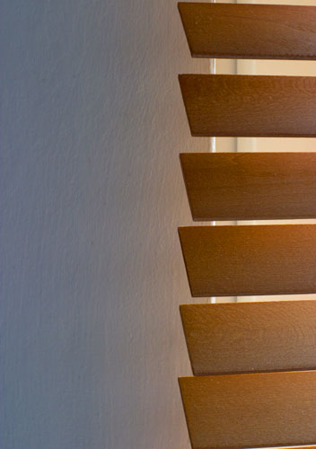 The light reflecting from this venetian blind is projecting the wood's colour onto the wall.