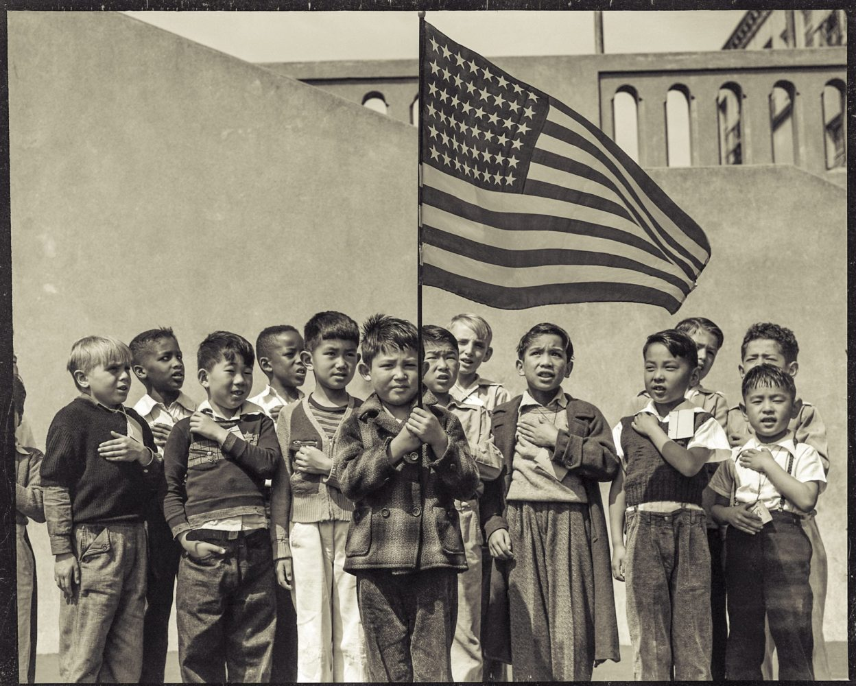 """Flag of allegiance pledge at Raphael Weill Public School, Geary and Buchanan Streets, Children in families of Japanese ancestry were evacuated with their parents and will be housed for the duration in War Relocation Authority centers where facilities will be provided for them to continue their education."""" Dorothea Lange, 1942, San Francisco, California"""