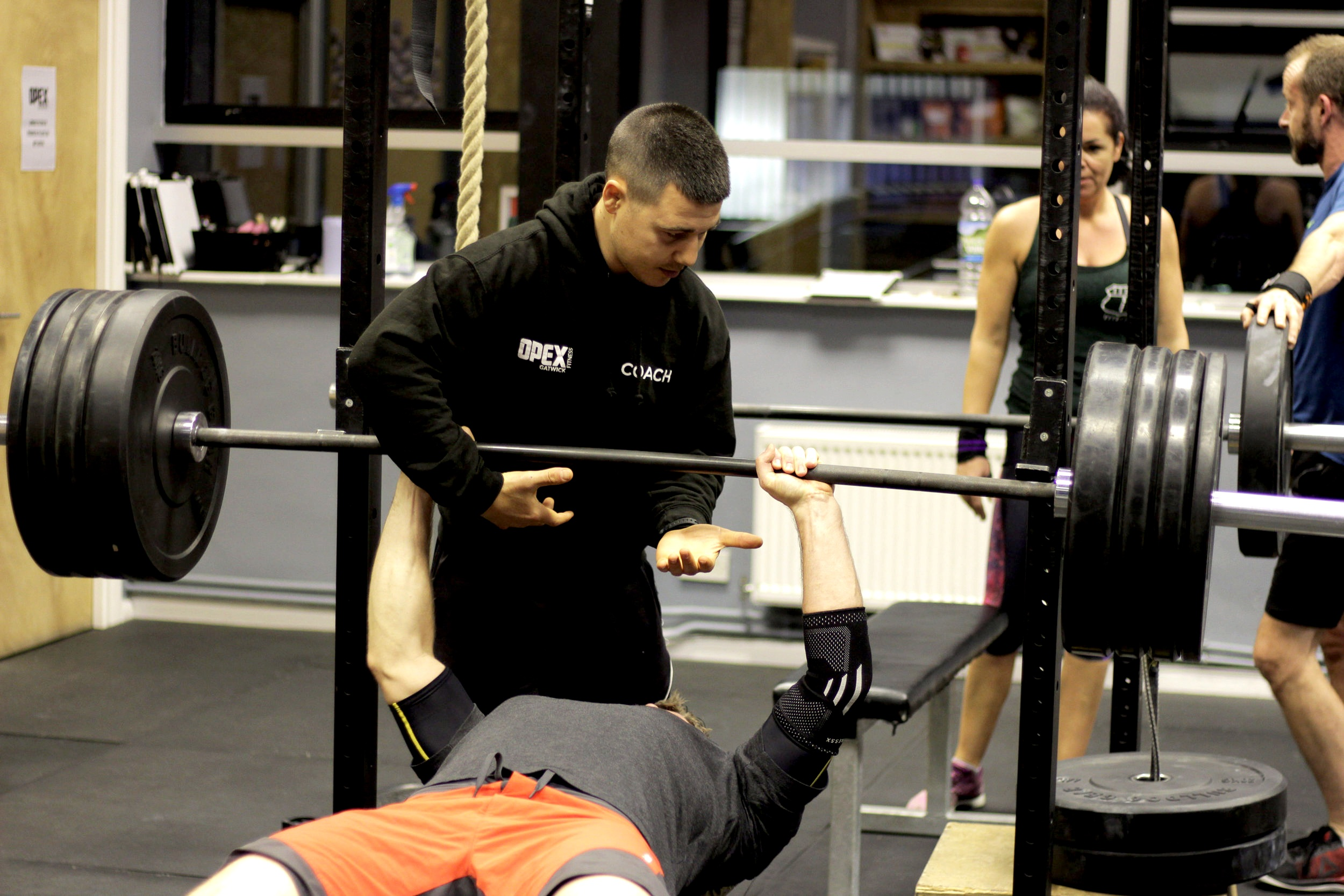 Personal Trainer Kris spotting during bench press