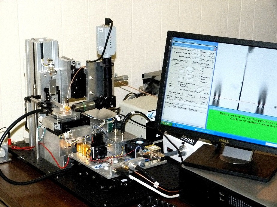 Fig.1. Vibr-2 spectrometer for general laboratory applications with a sample table movable in 2 directions (0.13 micron step) and a detector movable in the Z direction. The objective is focused on a surface of a periodic chip with two channels and a 50 microns probe and their reflection in the metal visible on the monitor screen. Parameters for experimental scans are specified on the left of the screen.