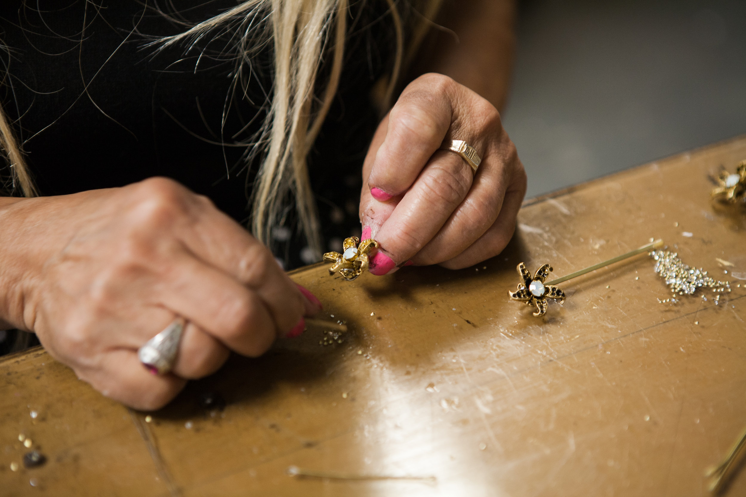 In the studio, there is a technician who works on the cutting, manipulating, and soldering and two pasters who have expertise in how an earring gets glued as opposed to how a button gets glued.