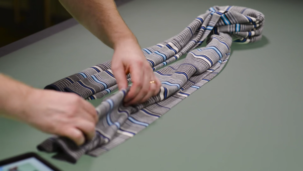 Lay the scarf back down and make sure the knot has a round, deep body to it. When laying out the ends of the scarf, use precision and attempt to taper them in a way that gives the illusion of gravity pulling it down and crease the fabric in a way that creates a layered effect.