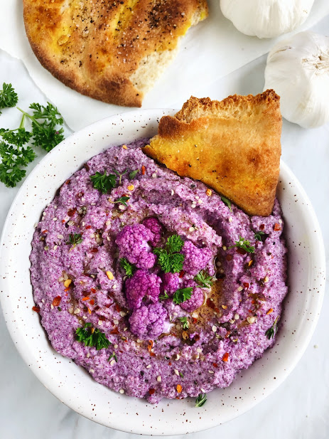 Purple Cauliflower Hummus - 2-3 cups of purple cauliflower florets1/3 cup tahini1/4 olive oil1 tbsp honey 1/2 squeezed lemon juice1/4 chopped minced onion2-3 cloves minced garlicSalt and pepper to tasteMETHODMix all ingredients into a food processor until well mixed.I topped it with some olive oil, fresh thyme and parsley, chilli flakes, @manitobaharvestHemp hearts, and served it with a side of baked naan with @simplyorganicfoods turmeric and Italian seasoning.