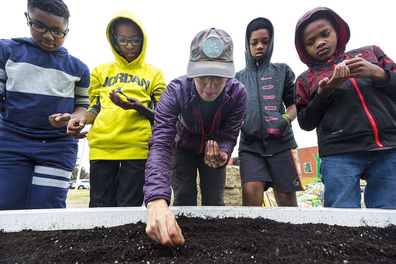 Erika Hansen of Big Green assists Highland Oaks Elementary students (left to right,) Kolin Pratcher, Elijah Smith, Deante Strong, and Xavier Smith in planting in their garden for local Planting Day in  Memphis, TN