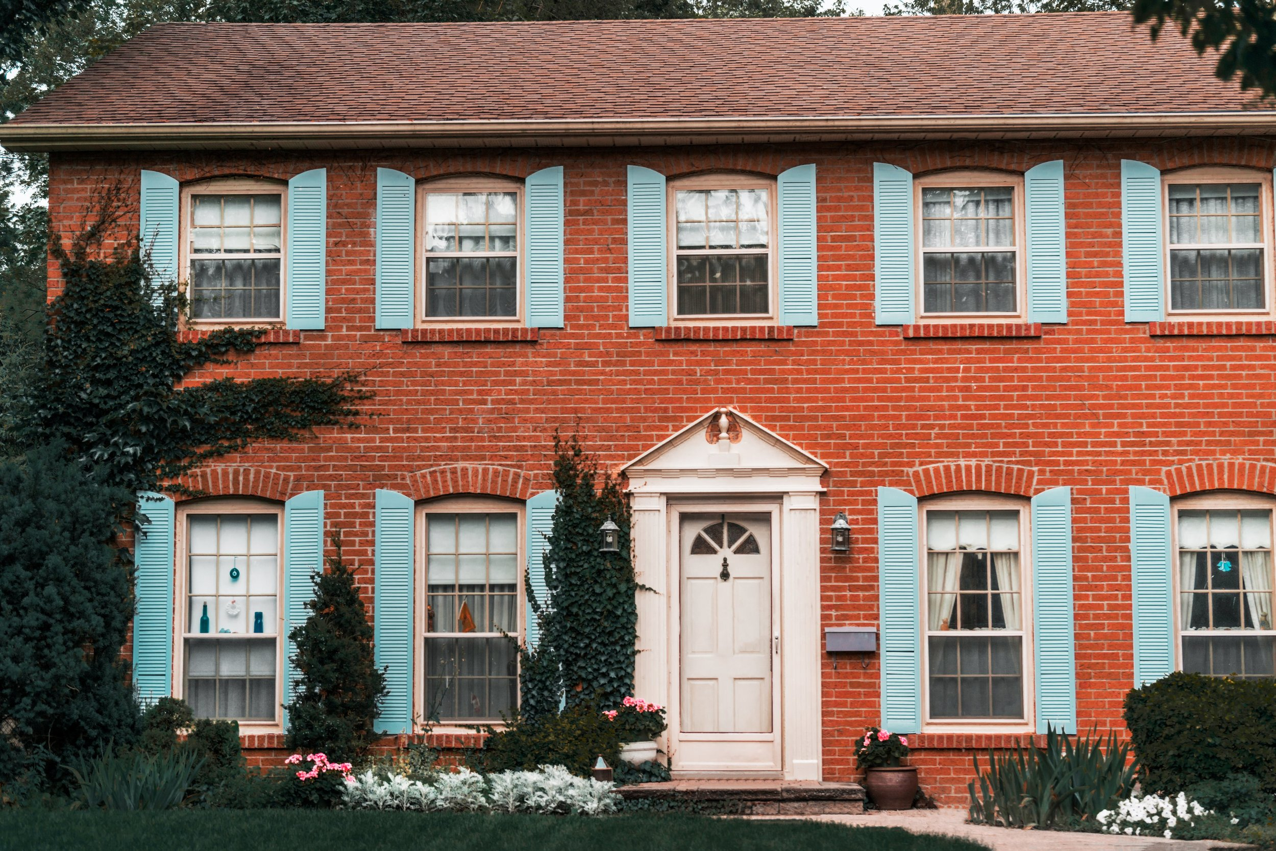 Red brick house with blue shutters.