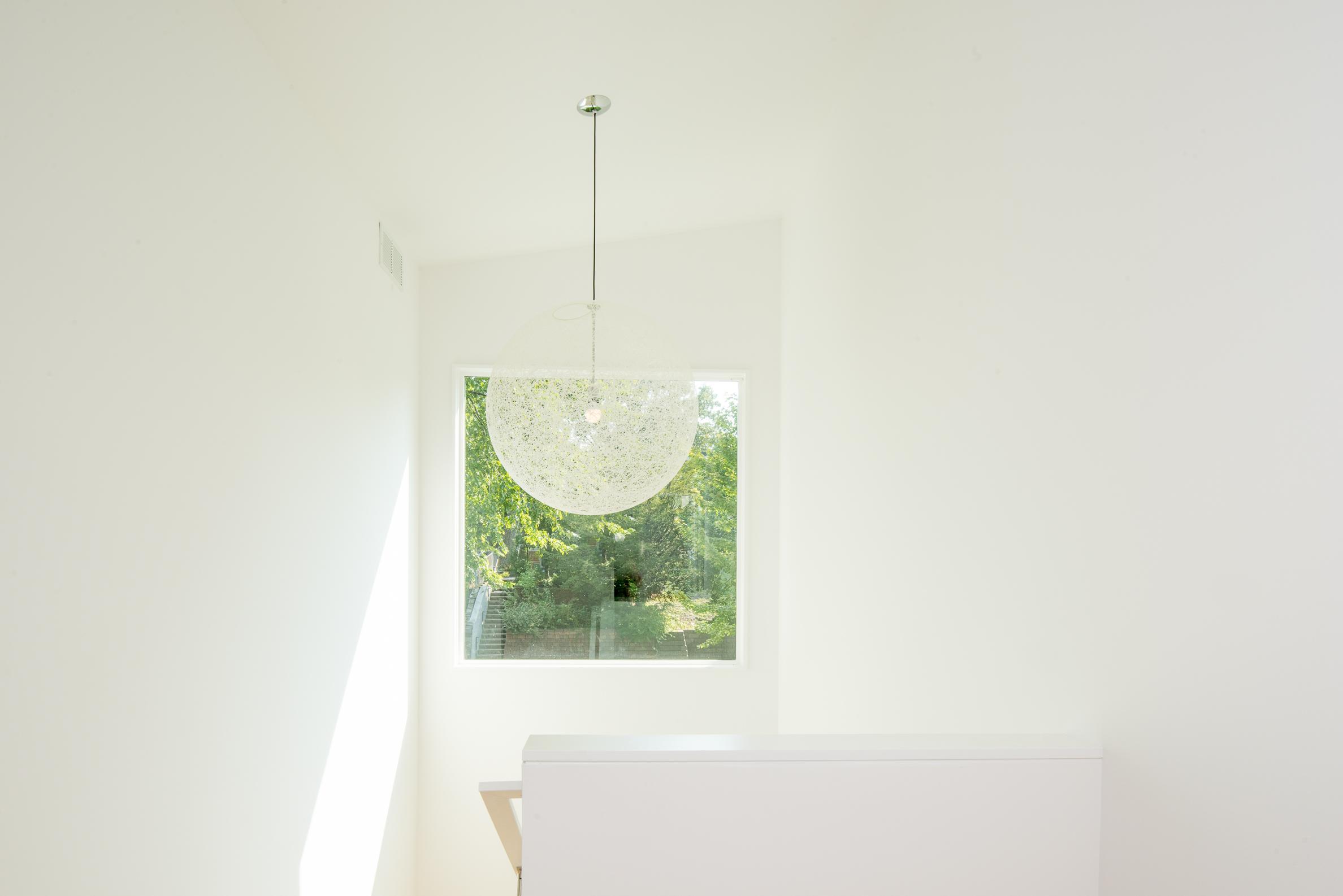 White stair atrium with modern chandelier