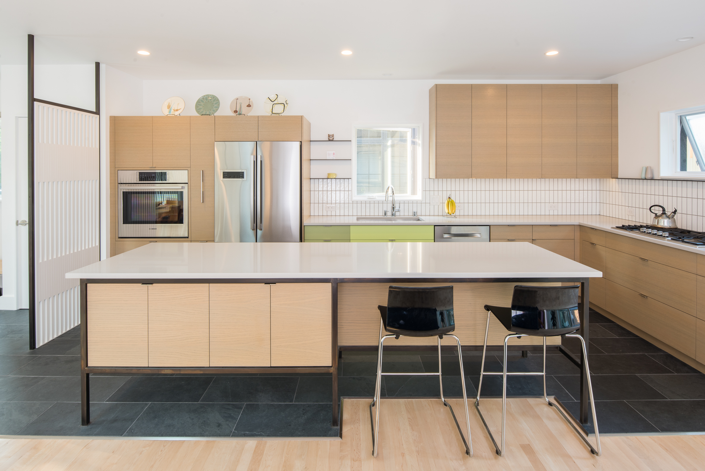 Custom mid-century kitchen design with colorful cabinetry and steel accents