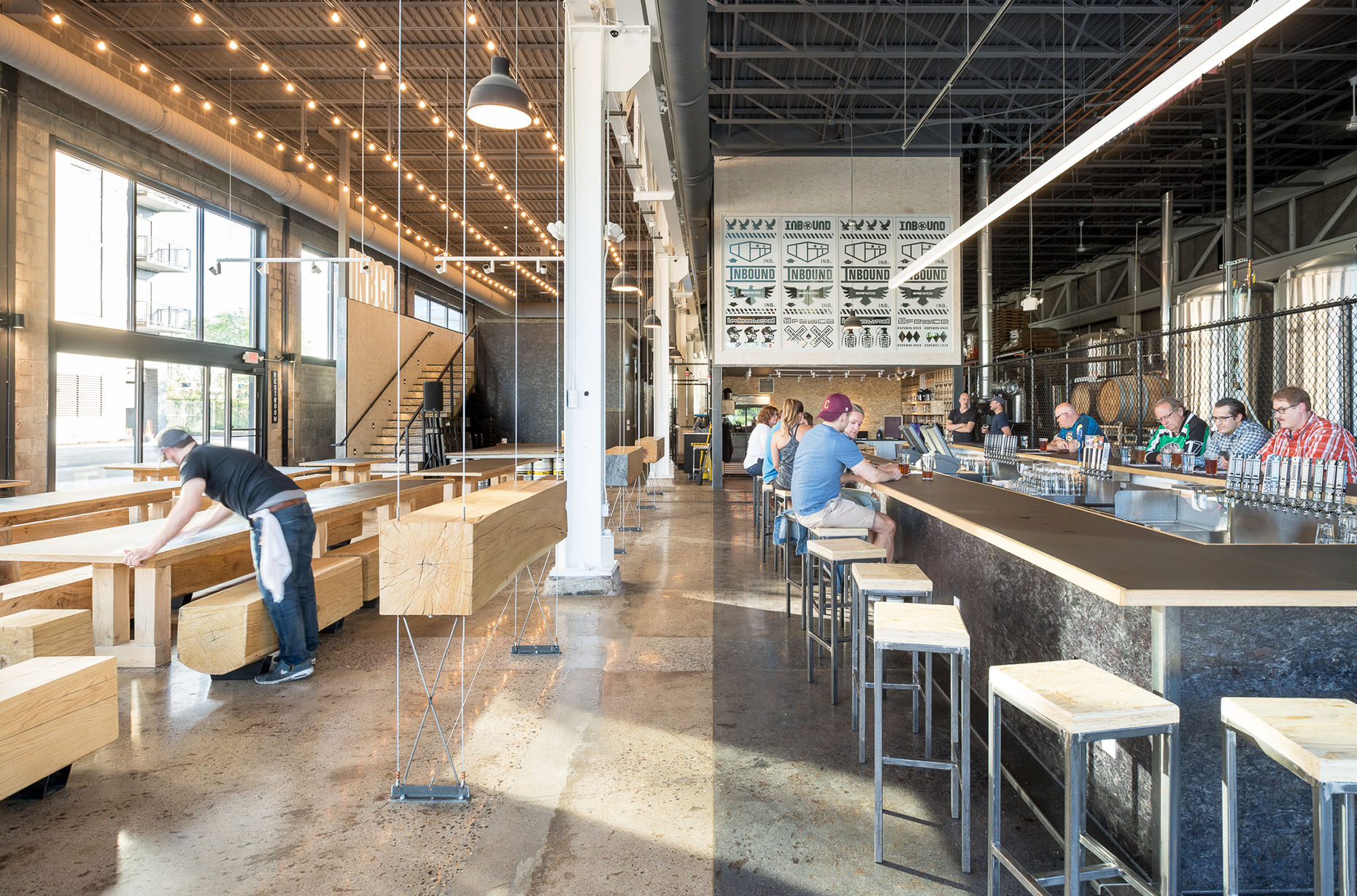 Modern industrial brewery with custom wood tables and standing drink rails.