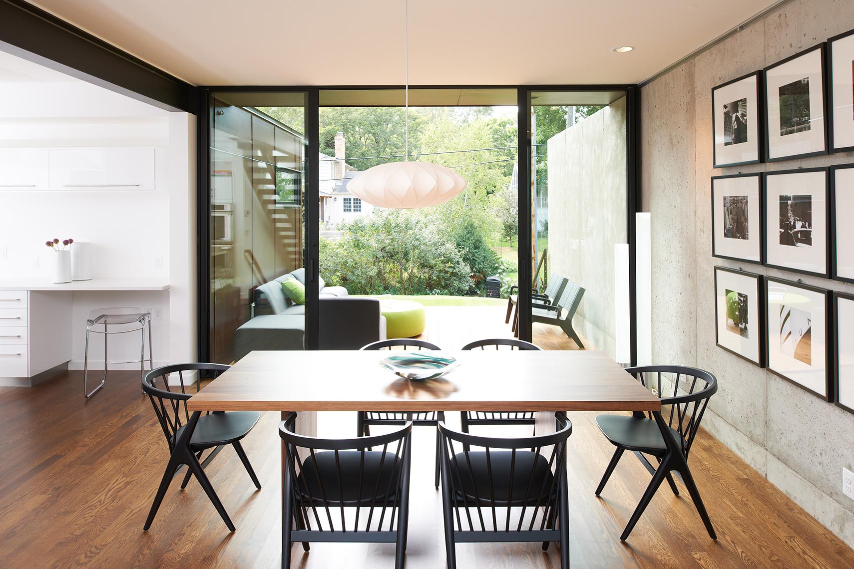 Modern dining room overlooking yard through full-height sliding glass door