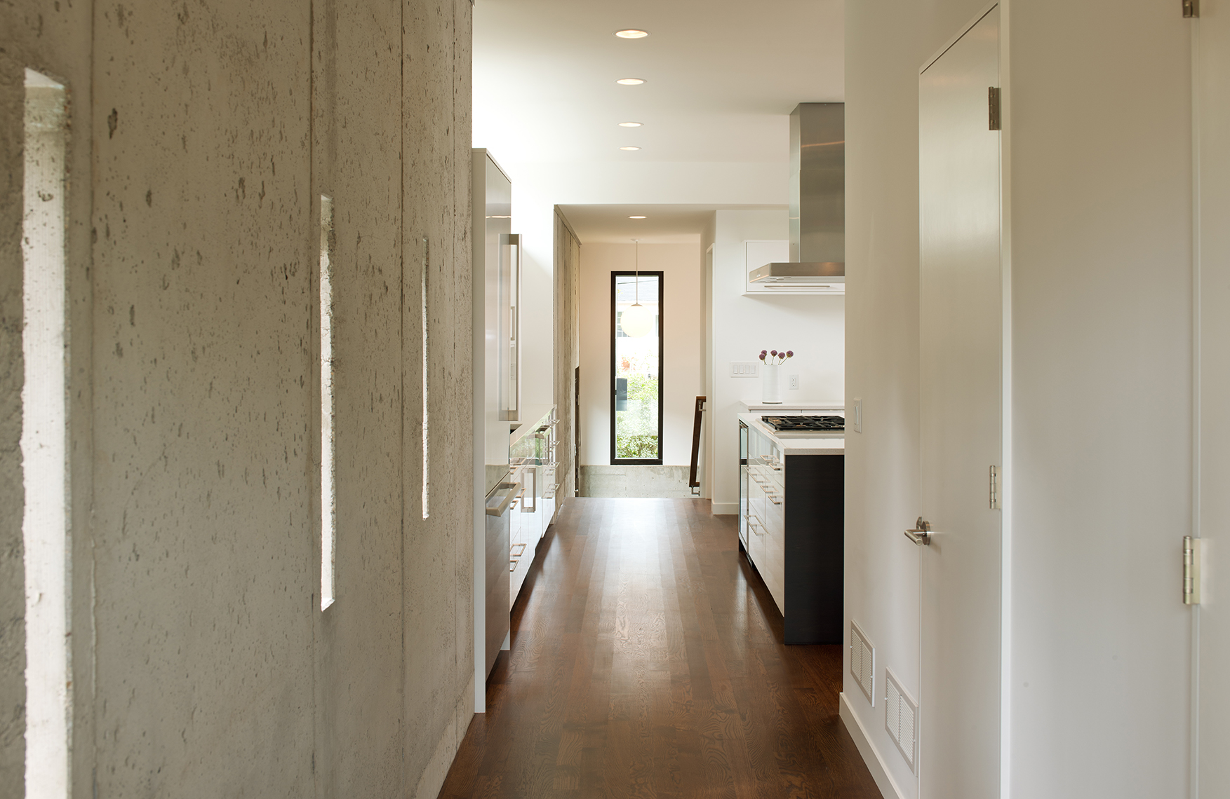 Hallway through kitchen on modern home remodel with exposed concrete wall