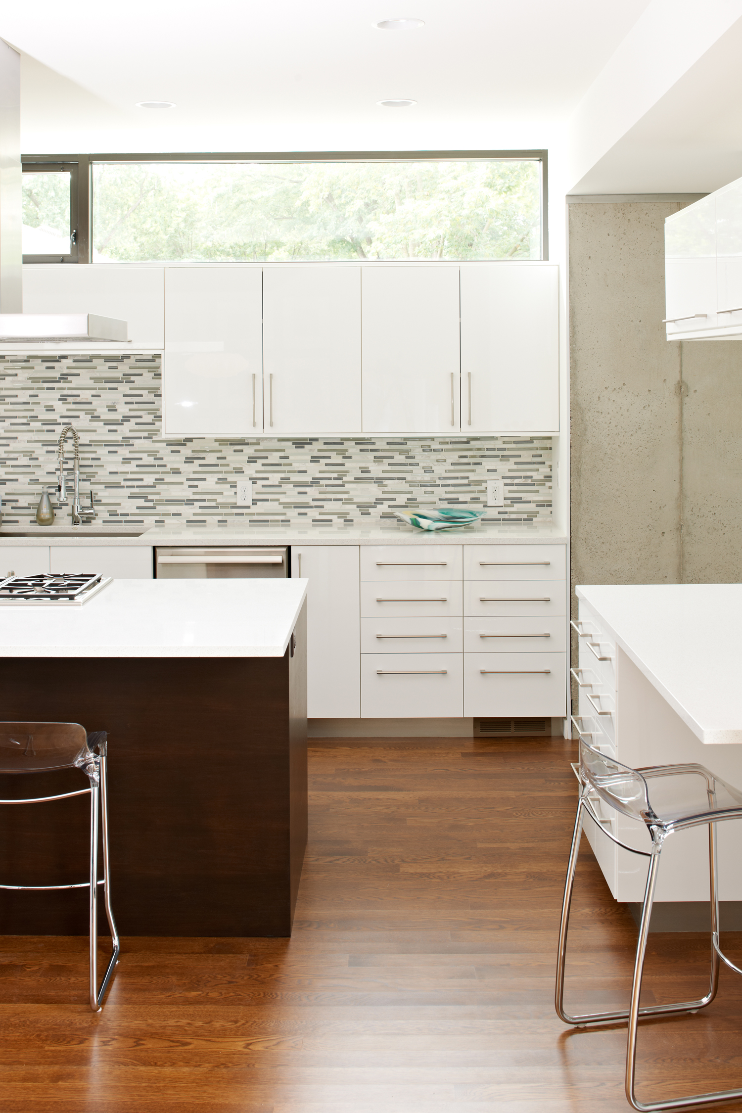 Modern kitchen with white cabinetry and grey tile backsplash