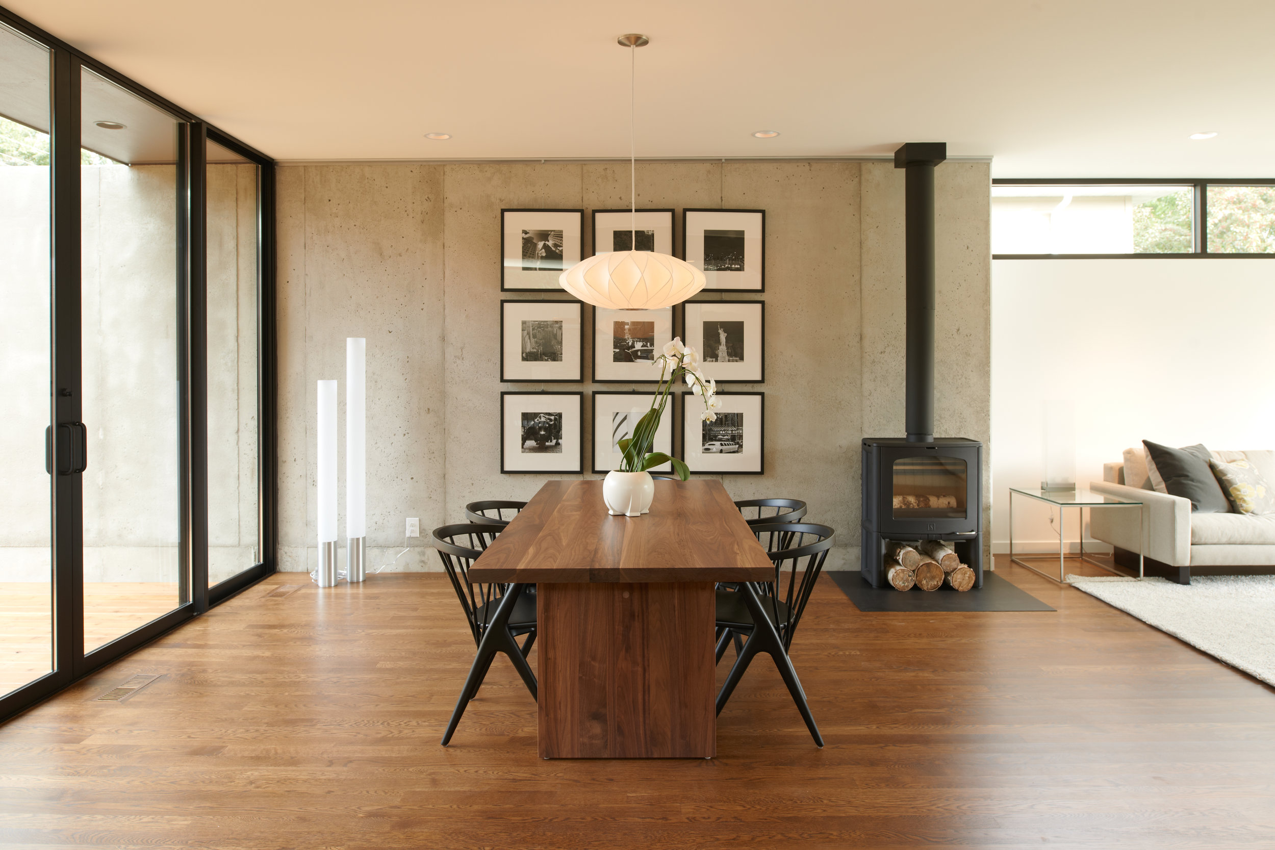 Modern dining room with wood floor and concrete wall