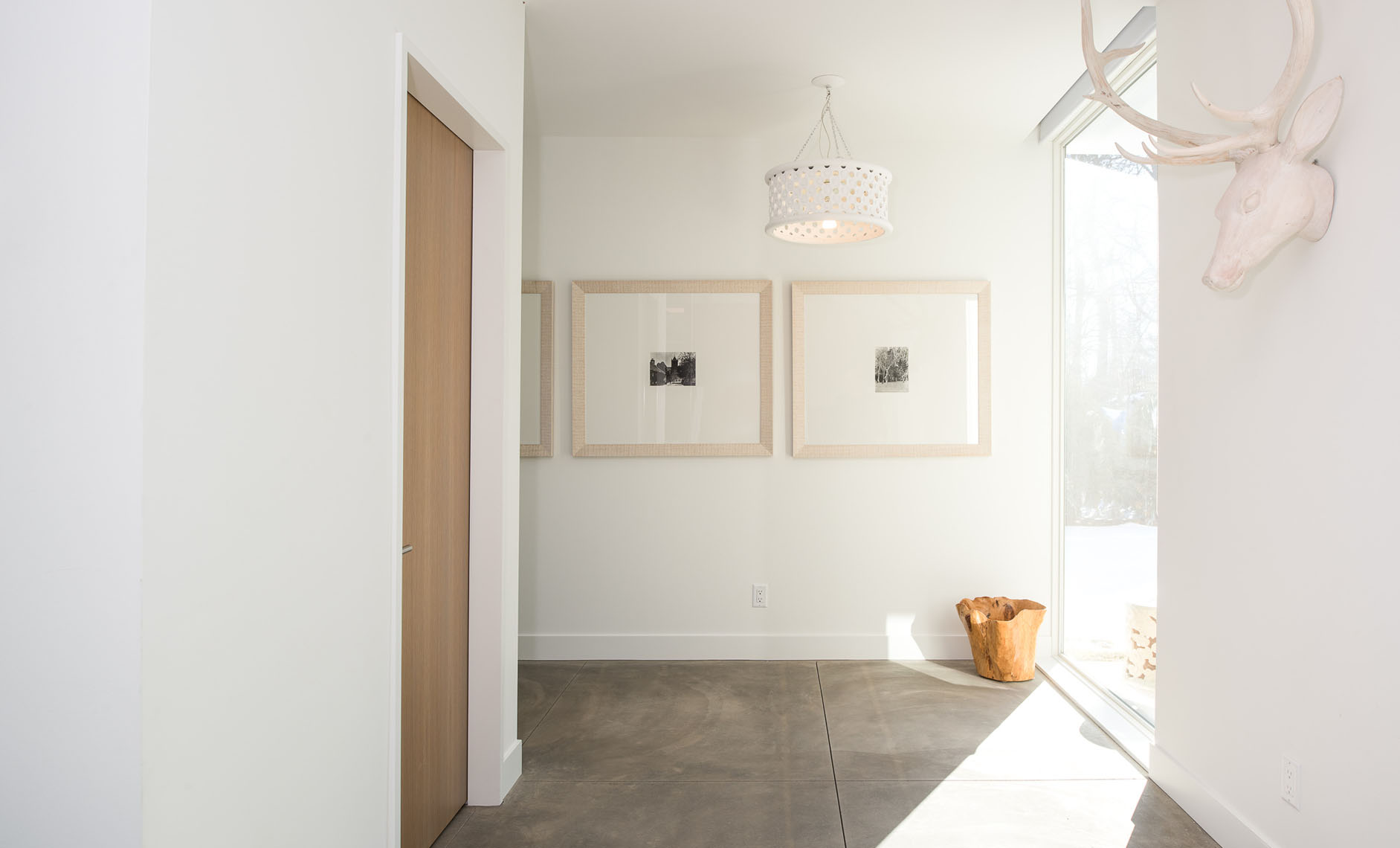 Hallway with a concrete floor and white walls
