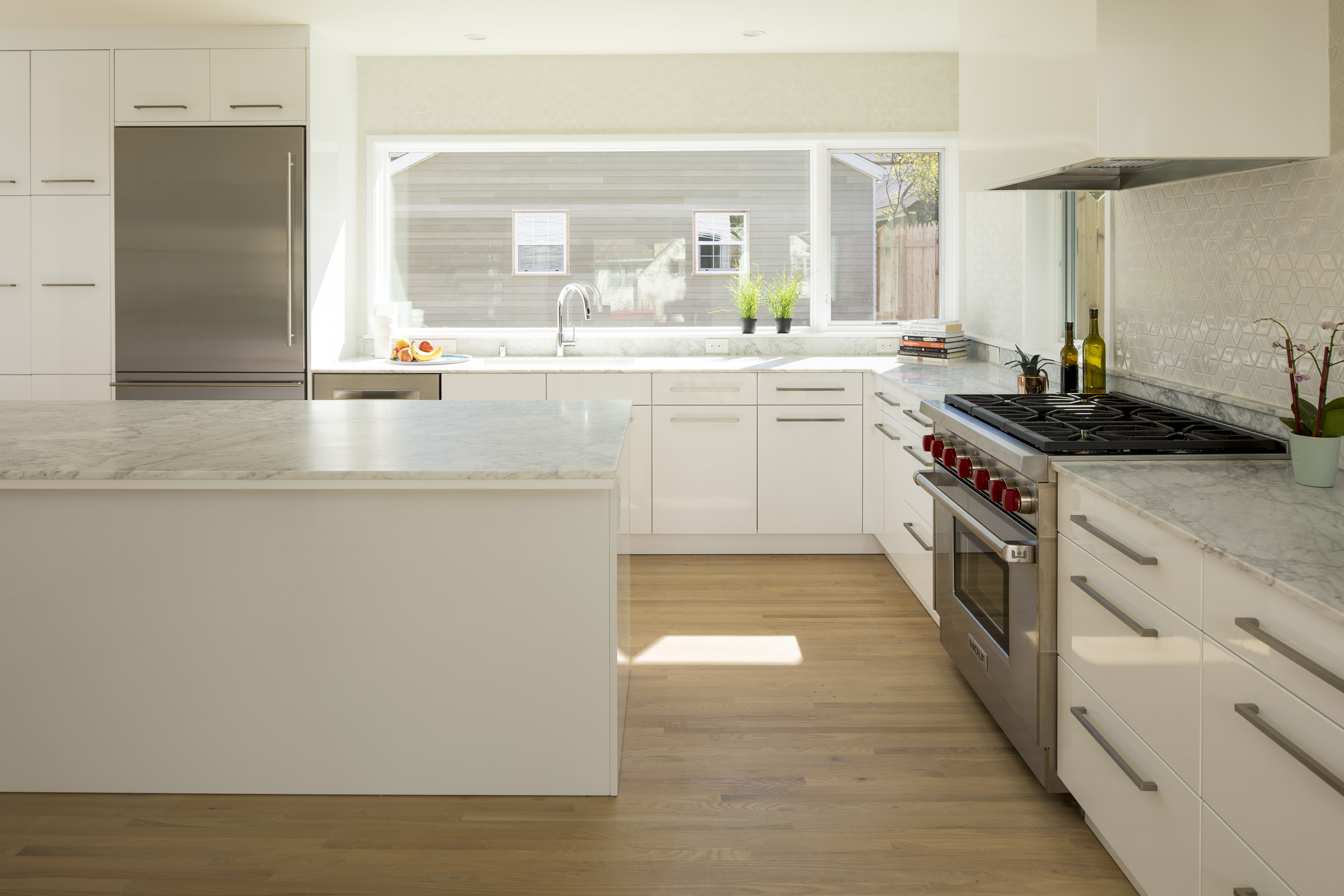 Modern kitchen remodel with white cabinetry and marble countertops