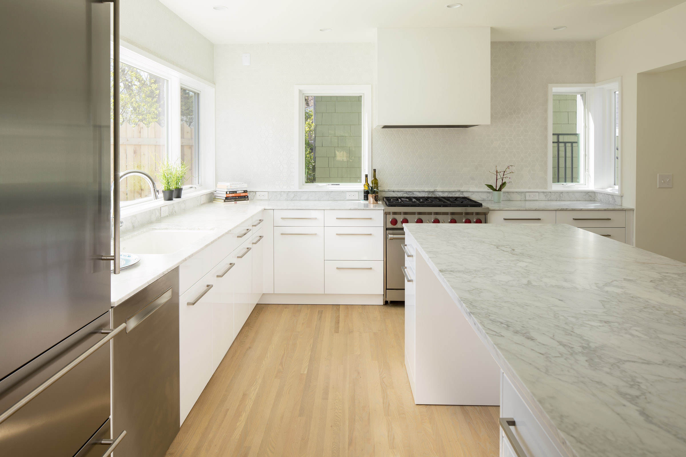 Modern white kitchen remodel with marble countertops and tile backsplash