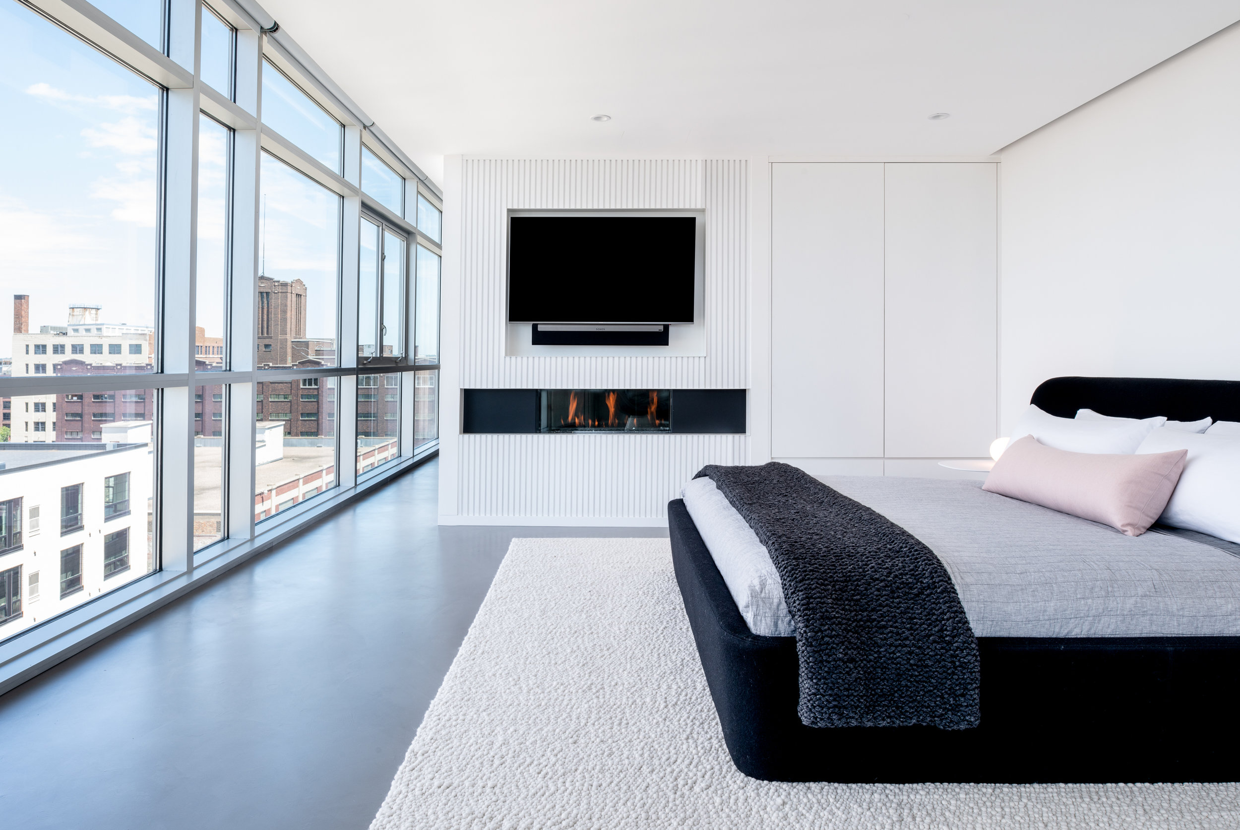 Modern monochrome bedroom with fireplace and recessed television