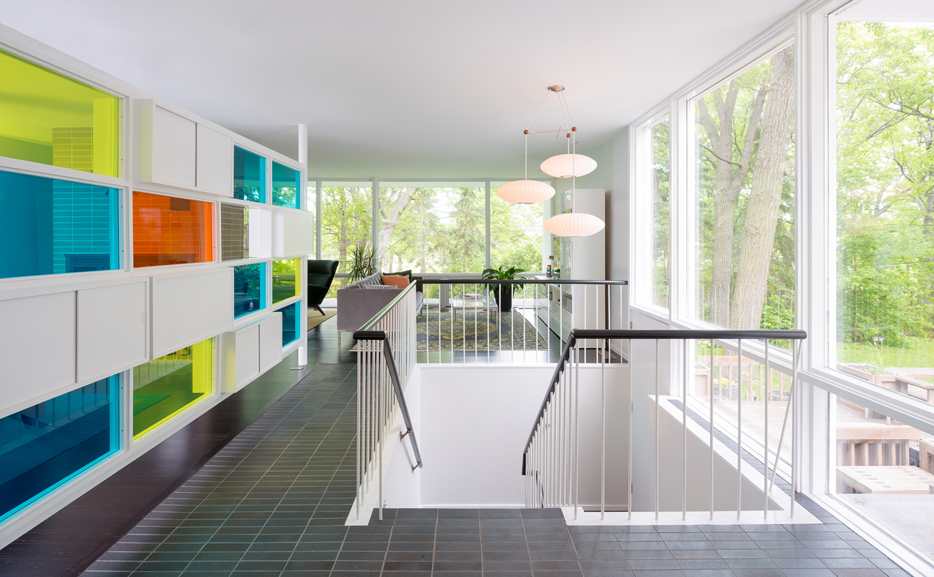 Tiled entry with colorful original divider wall and open stairwell