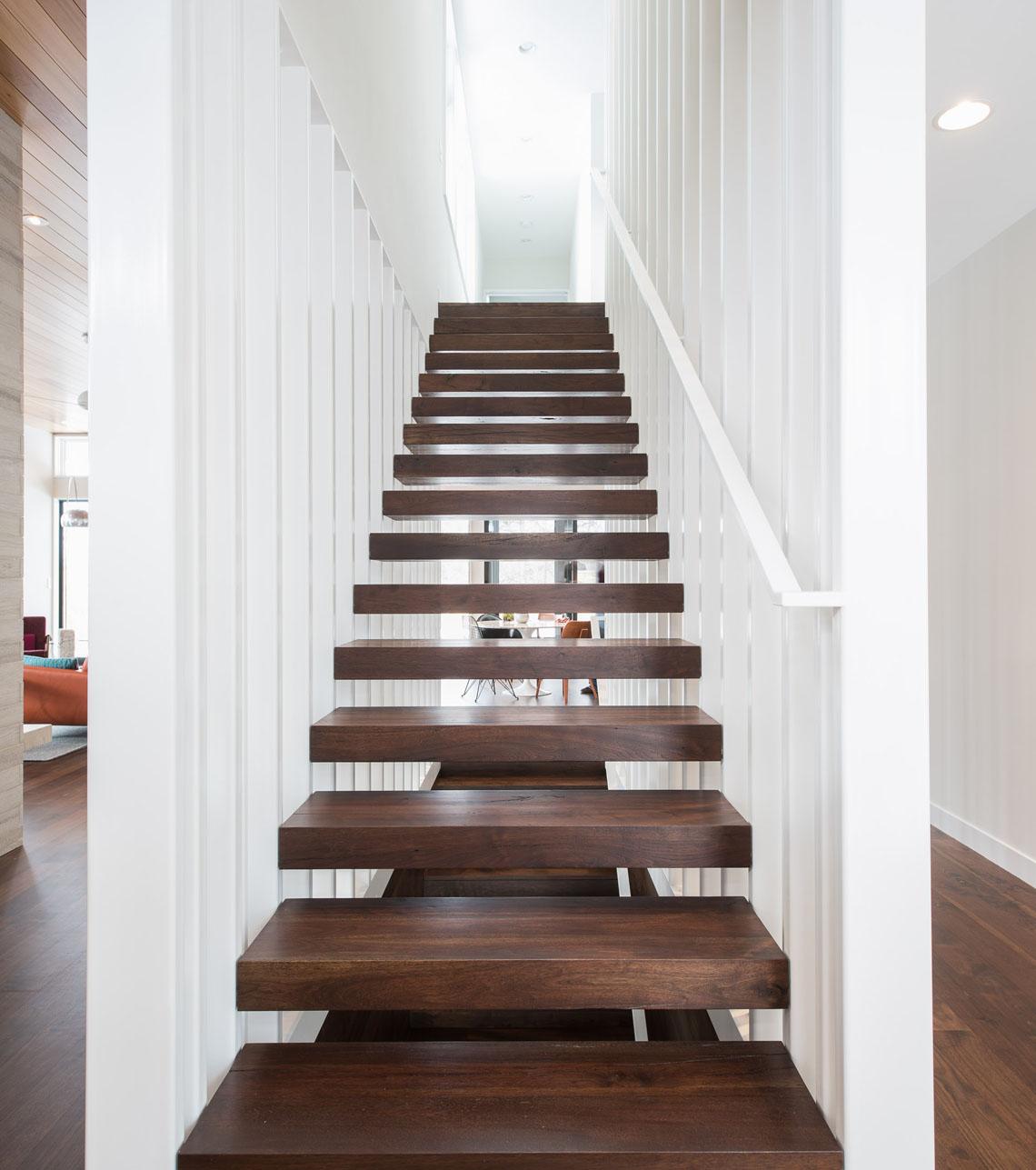 Custom sculptural floating tread stair with slat walls