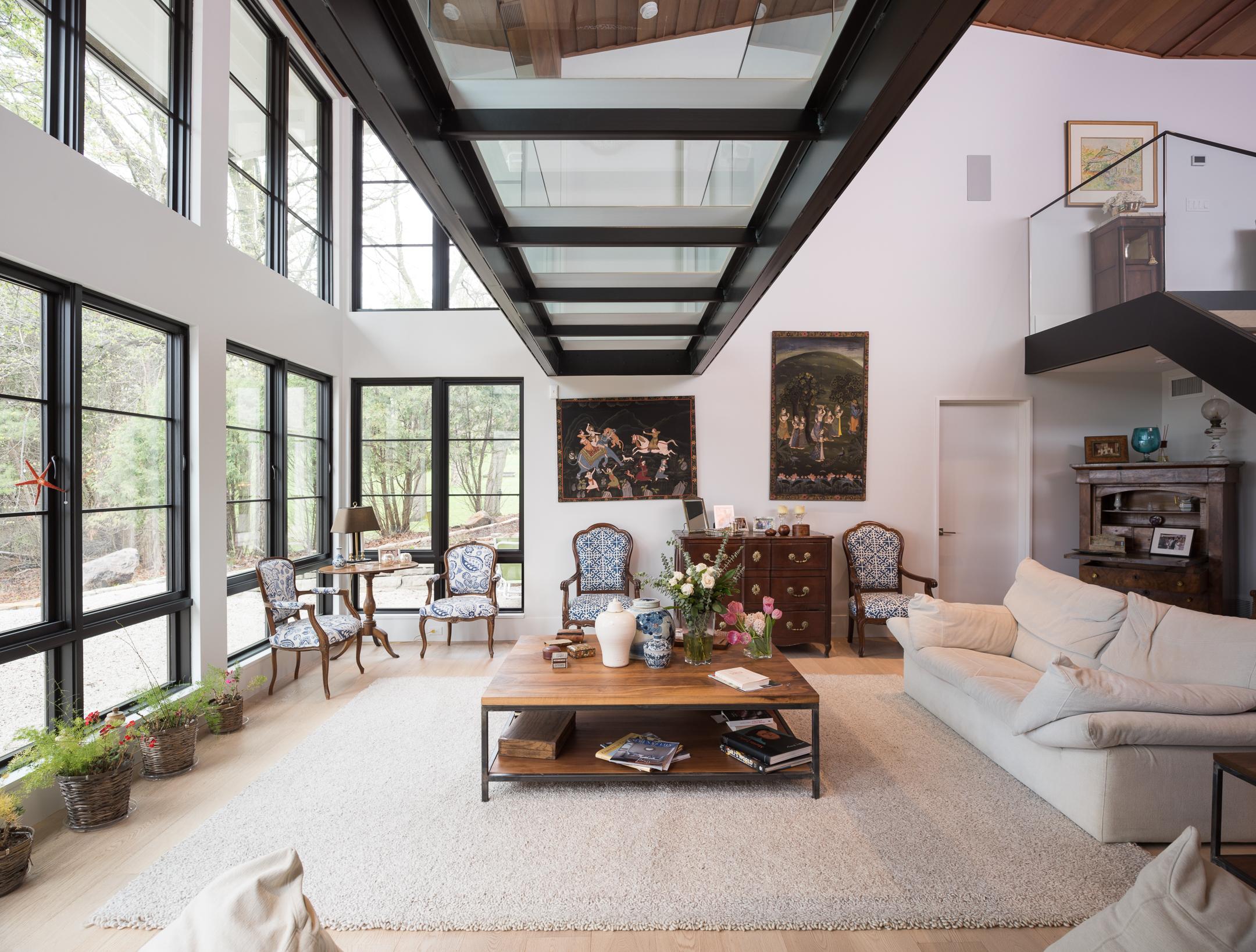Custom interior glass bridge over vaulted living room