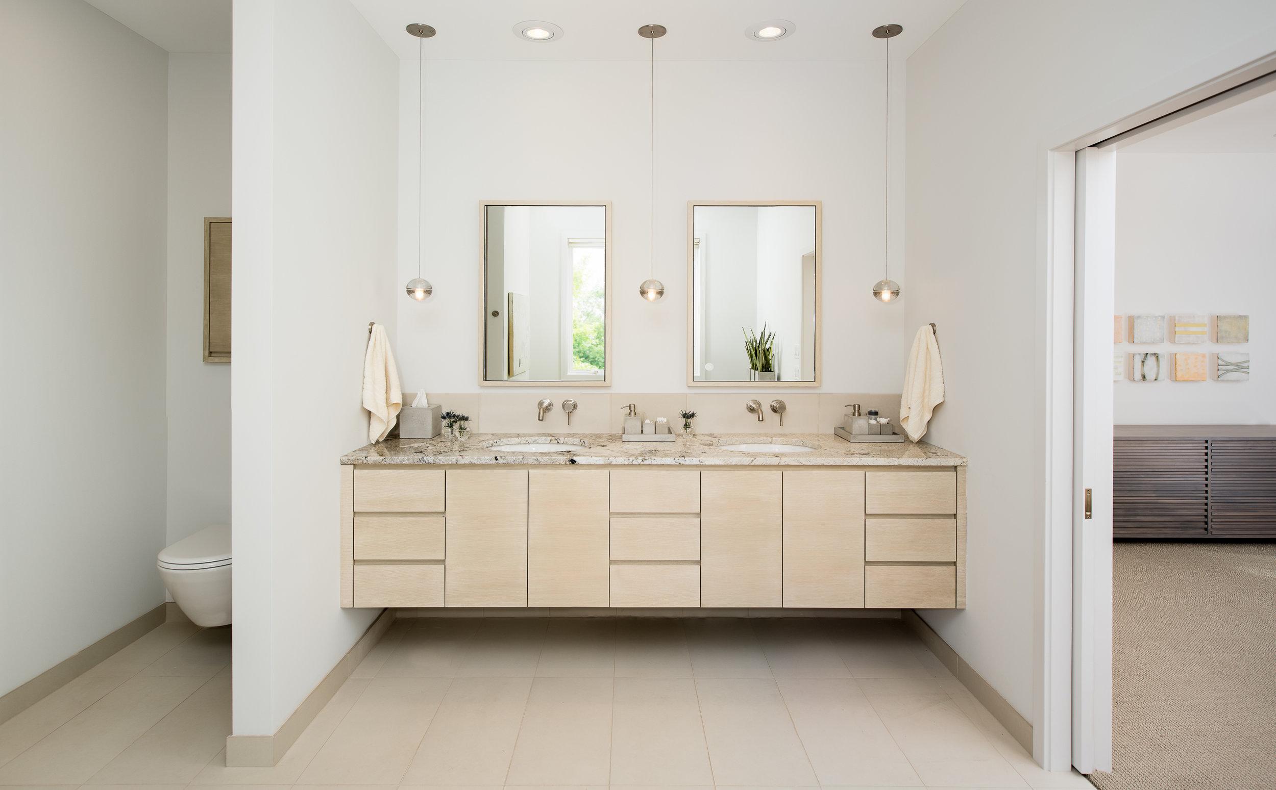 Custom floating master bathroom vanity with concealed toilet