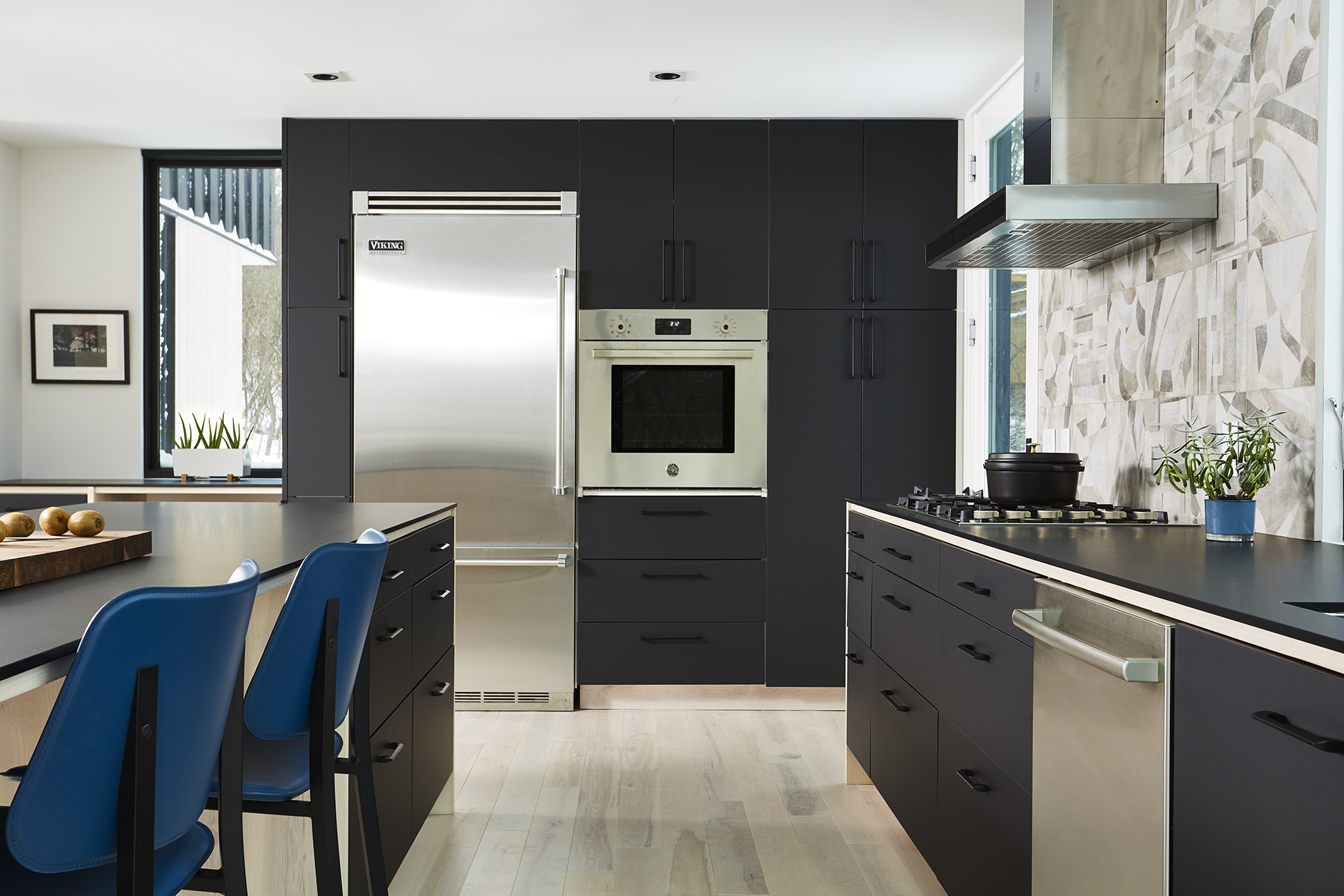 Modern monochromatic kitchen renovation with black cabinetry and wood accents