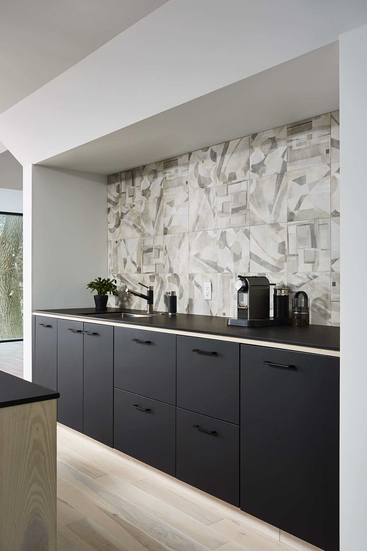 Recessed kitchen working area with graphic tile backsplash