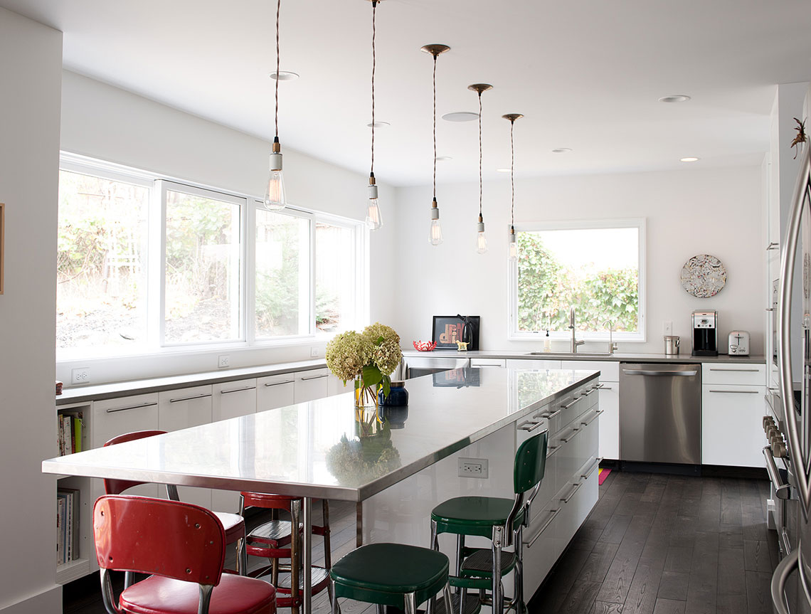 Modern white kitchen renovation with edison bulbs over large center island