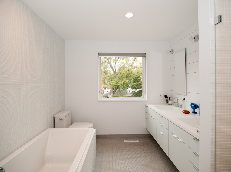 Modern bathroom renovation with tiled walls and custom floating vanity