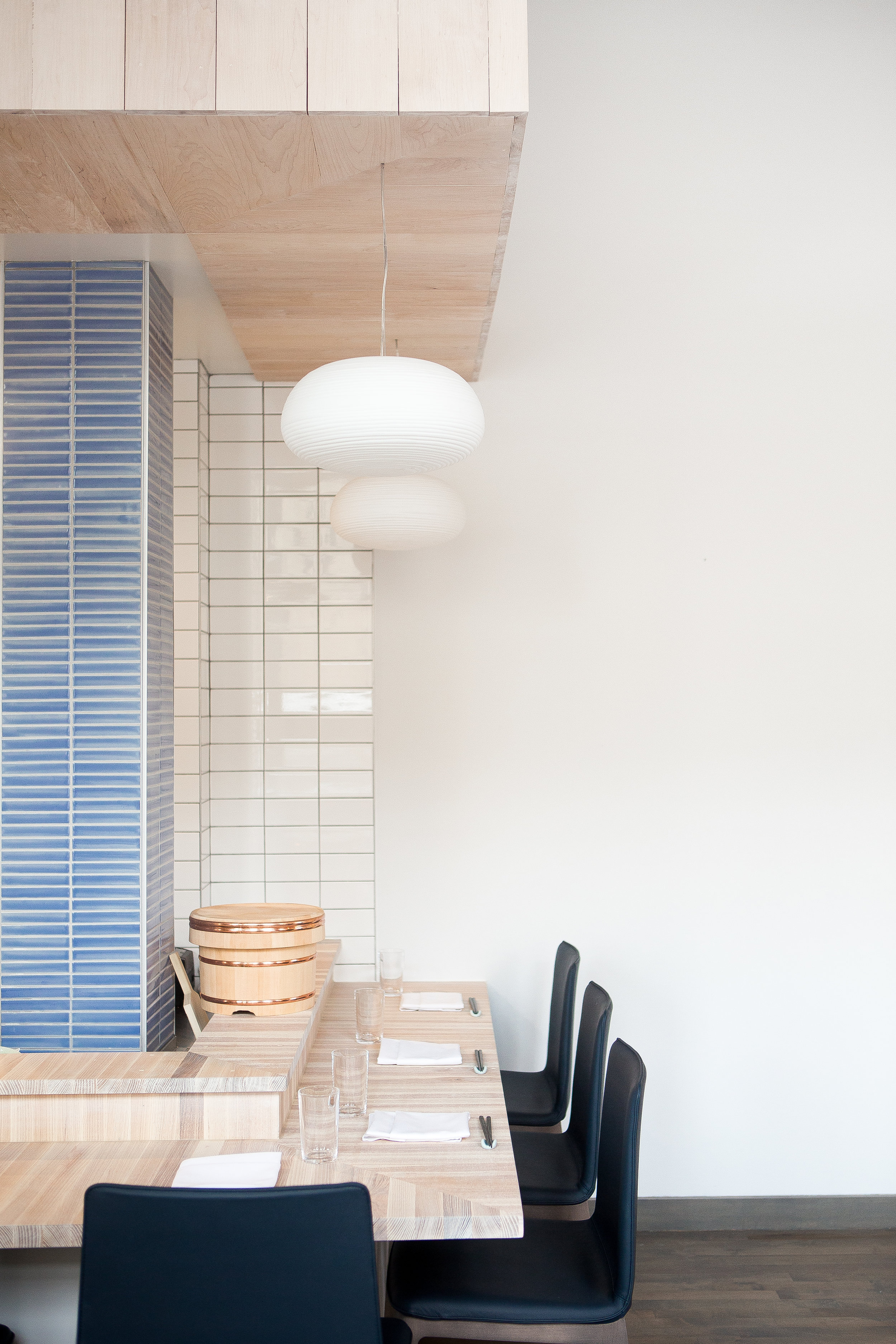 custom wood bar in restaurant with horizontally stacked gridded tile