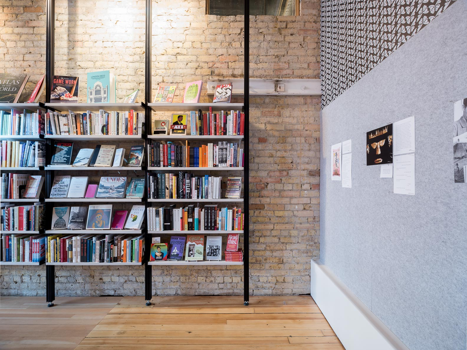 modern open steel and wood bookshelves against aged brick wall