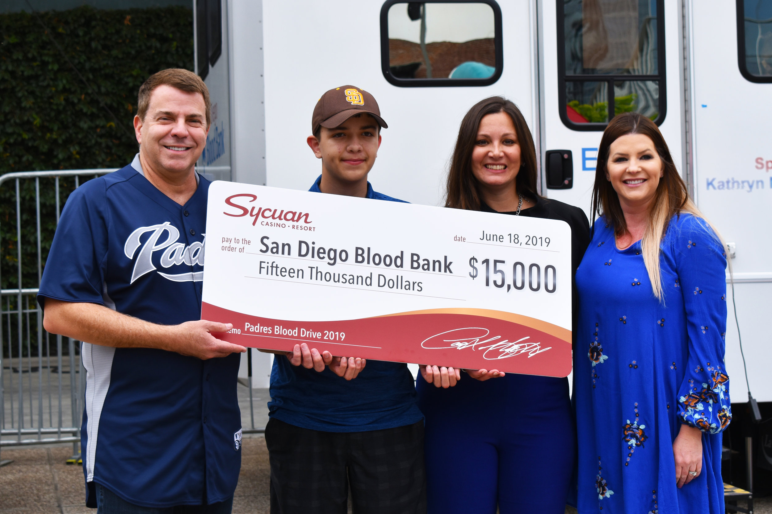 San Diego Blood Bank CEO David Wellis, Team Survivor Aidan Good, San Diego Blood Bank Vice President of Development Sherry Serio smile with a giant check from presenting sponsor, Sycuan Casino Resort's Community Development Manager Lauren Morrow.
